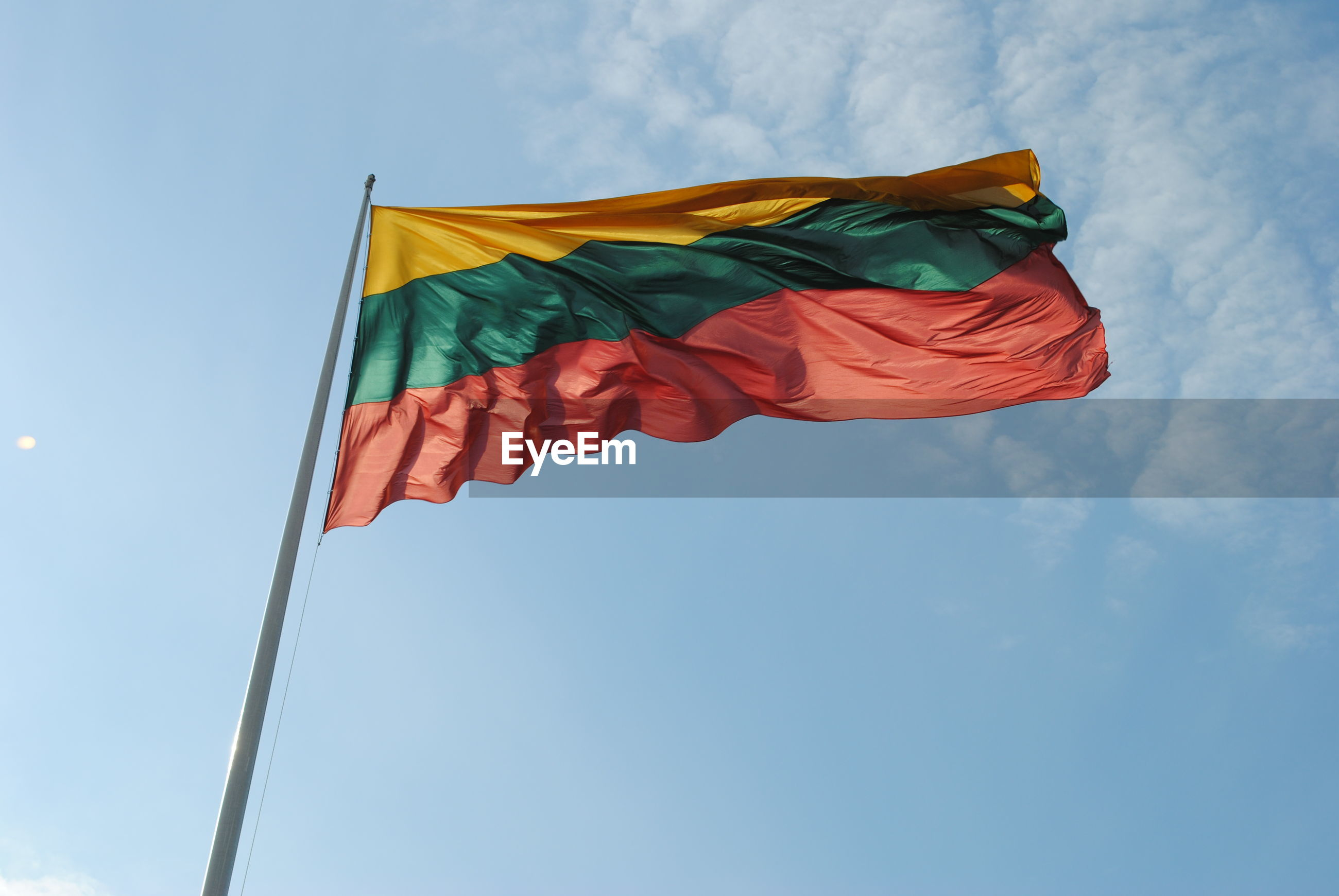 Low angle view of lithuanian flag waving against sky
