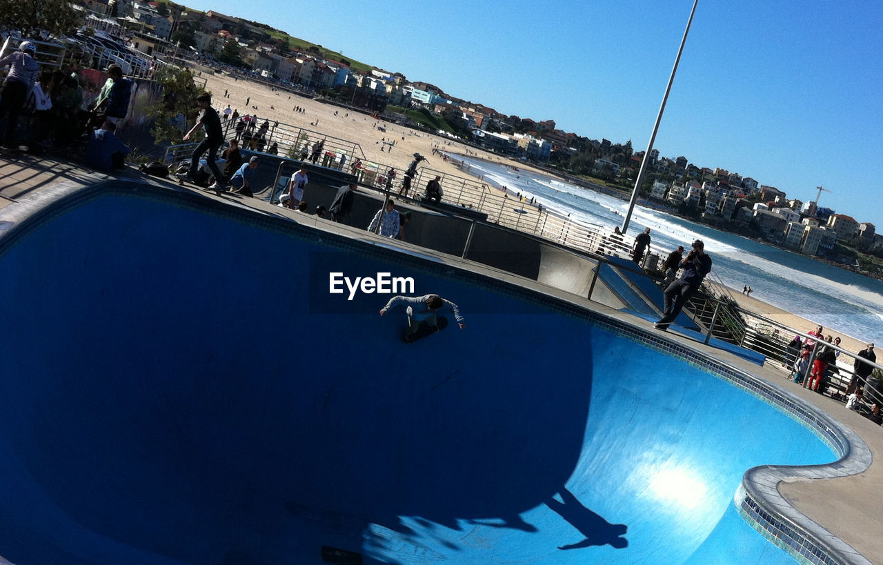 real people, day, high angle view, leisure activity, water, sunlight, clear sky, blue, architecture, built structure, men, outdoors, large group of people, lifestyles, women, vacations, building exterior, swimming pool, skateboard park, nature, sky, people
