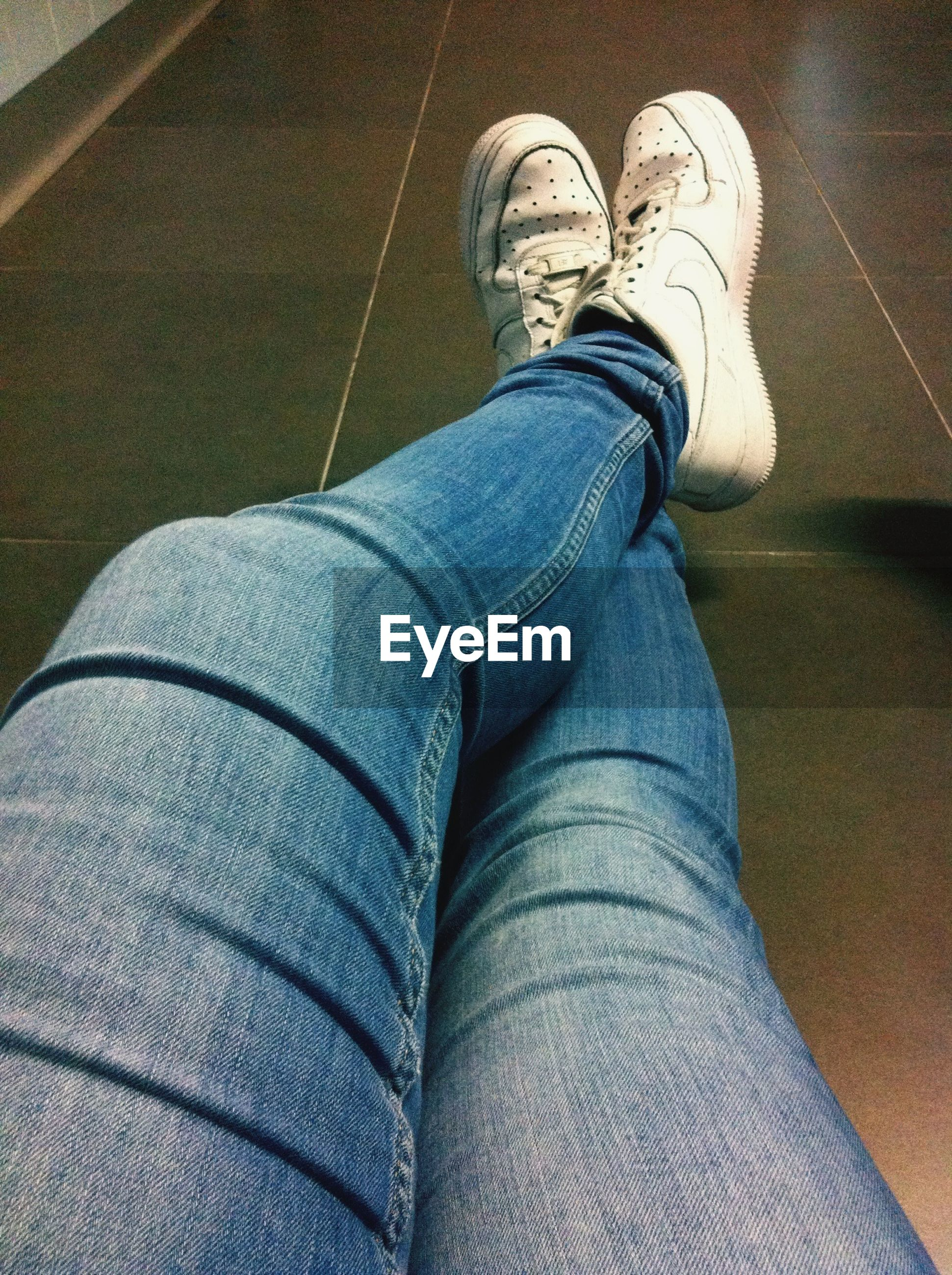 low section, person, jeans, shoe, lifestyles, personal perspective, casual clothing, human foot, indoors, footwear, men, standing, leisure activity, blue, sitting, high angle view, relaxation