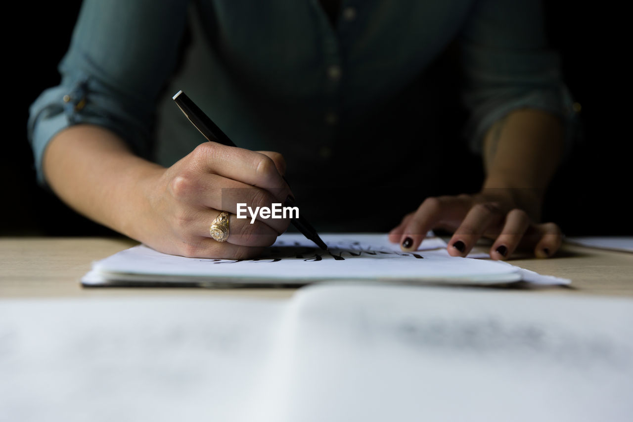 Midsection Of Woman Writing On Paper At Table