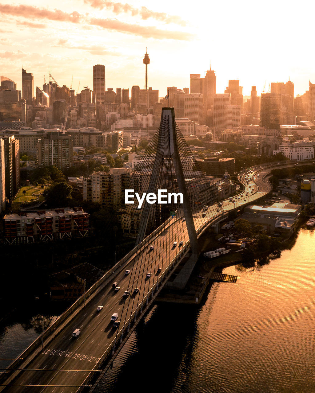 Aerial view of bridge over river against buildings in city during sunset
