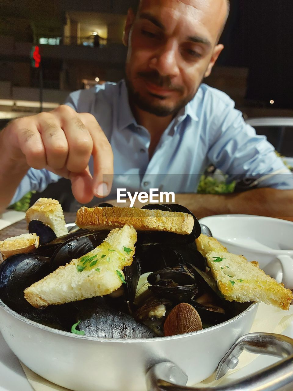 MIDSECTION OF MAN HAVING FOOD AT RESTAURANT