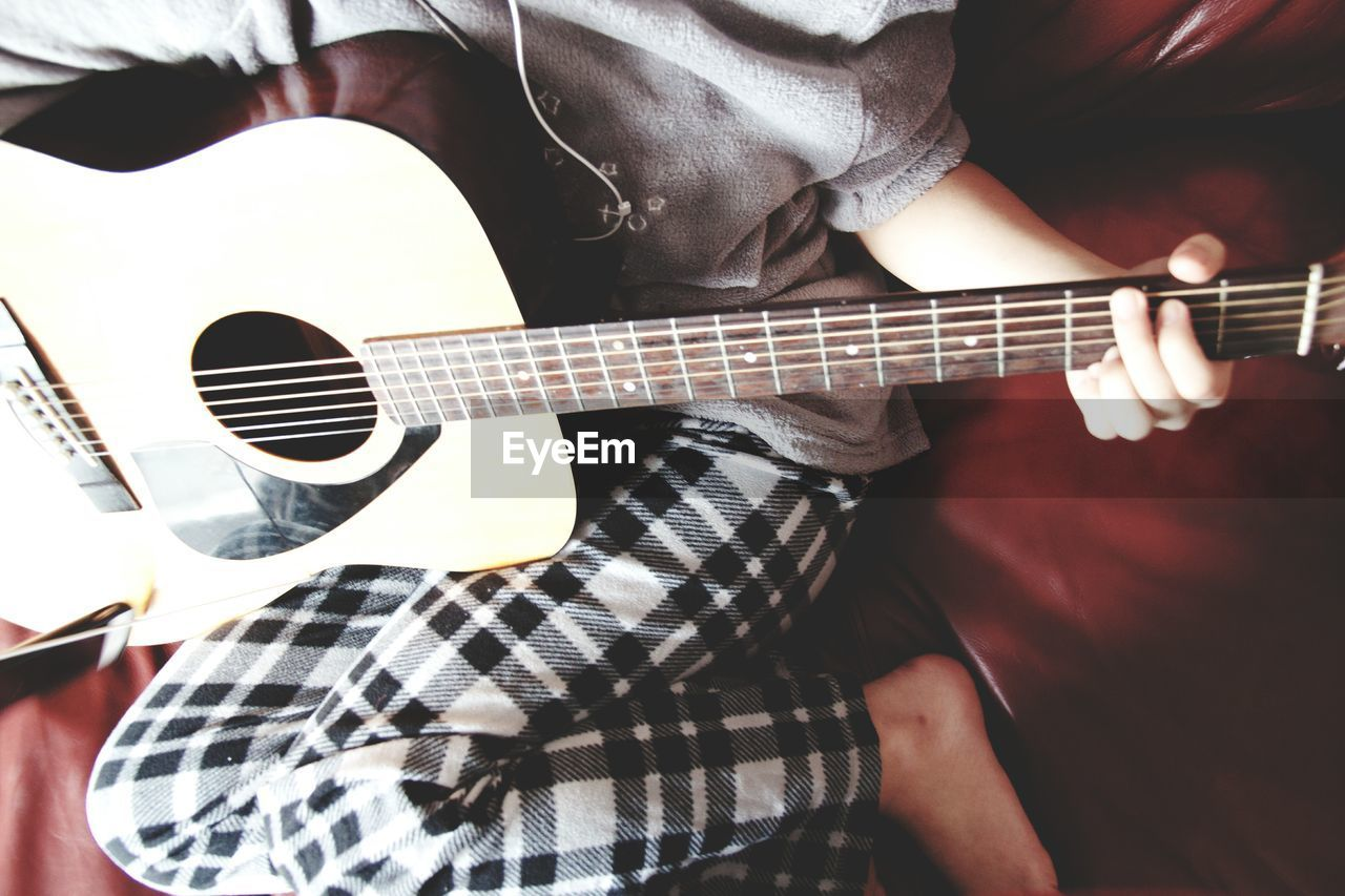 music, guitar, musical instrument, acoustic guitar, playing, arts culture and entertainment, musical instrument string, leisure activity, real people, plucking an instrument, fretboard, musician, indoors, string instrument, midsection, men, lifestyles, one person, electric guitar, close-up, day