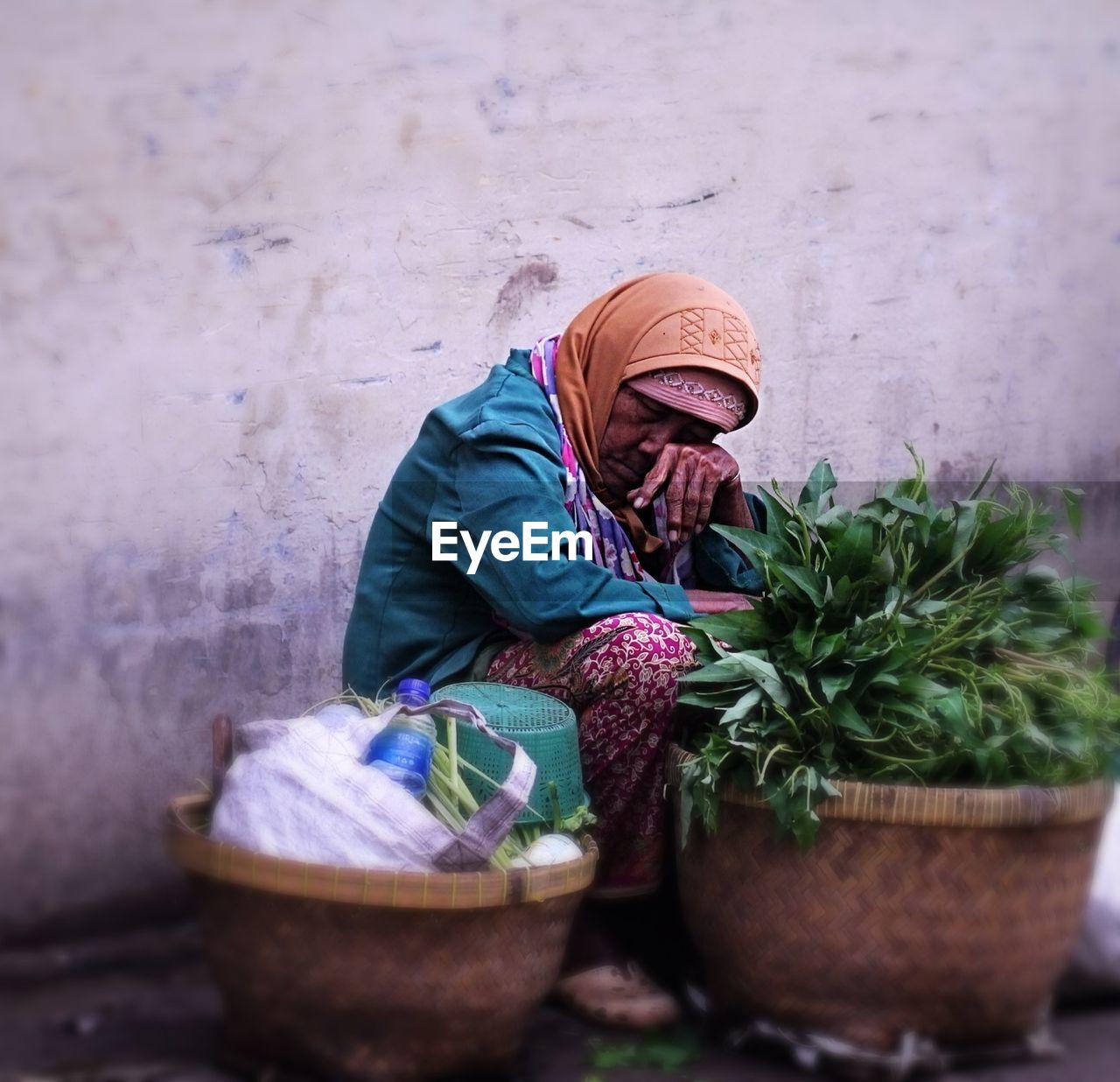 Senior vendor sleeping while selling leaf vegetables against wall