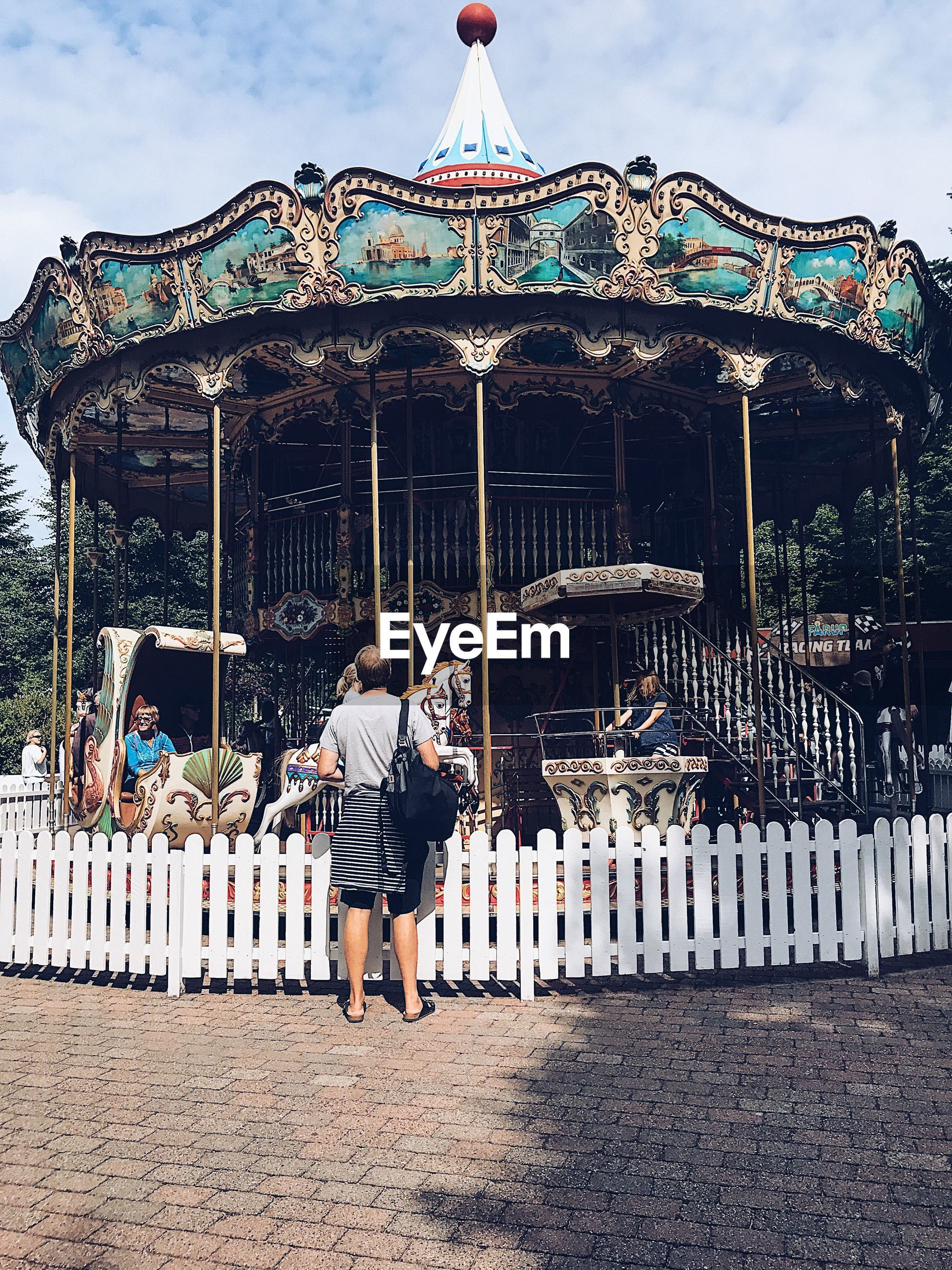 real people, leisure activity, amusement park, lifestyles, arts culture and entertainment, casual clothing, day, outdoors, rear view, built structure, full length, amusement park ride, standing, one person, sky, young women, men, carousel, young adult, architecture, people