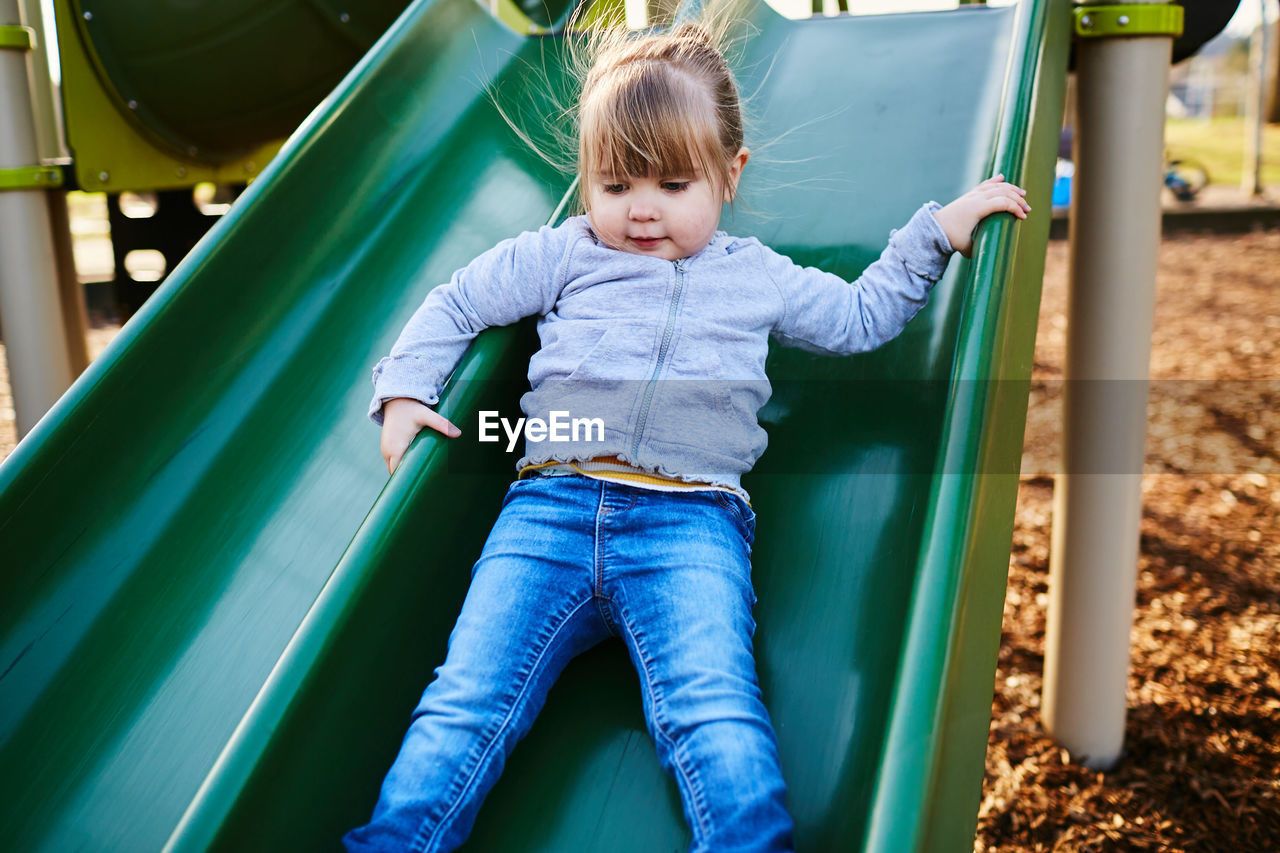 childhood, child, playground, real people, casual clothing, one person, slide - play equipment, leisure activity, innocence, lifestyles, outdoor play equipment, cute, playing, front view, three quarter length, day, outdoors, jungle gym