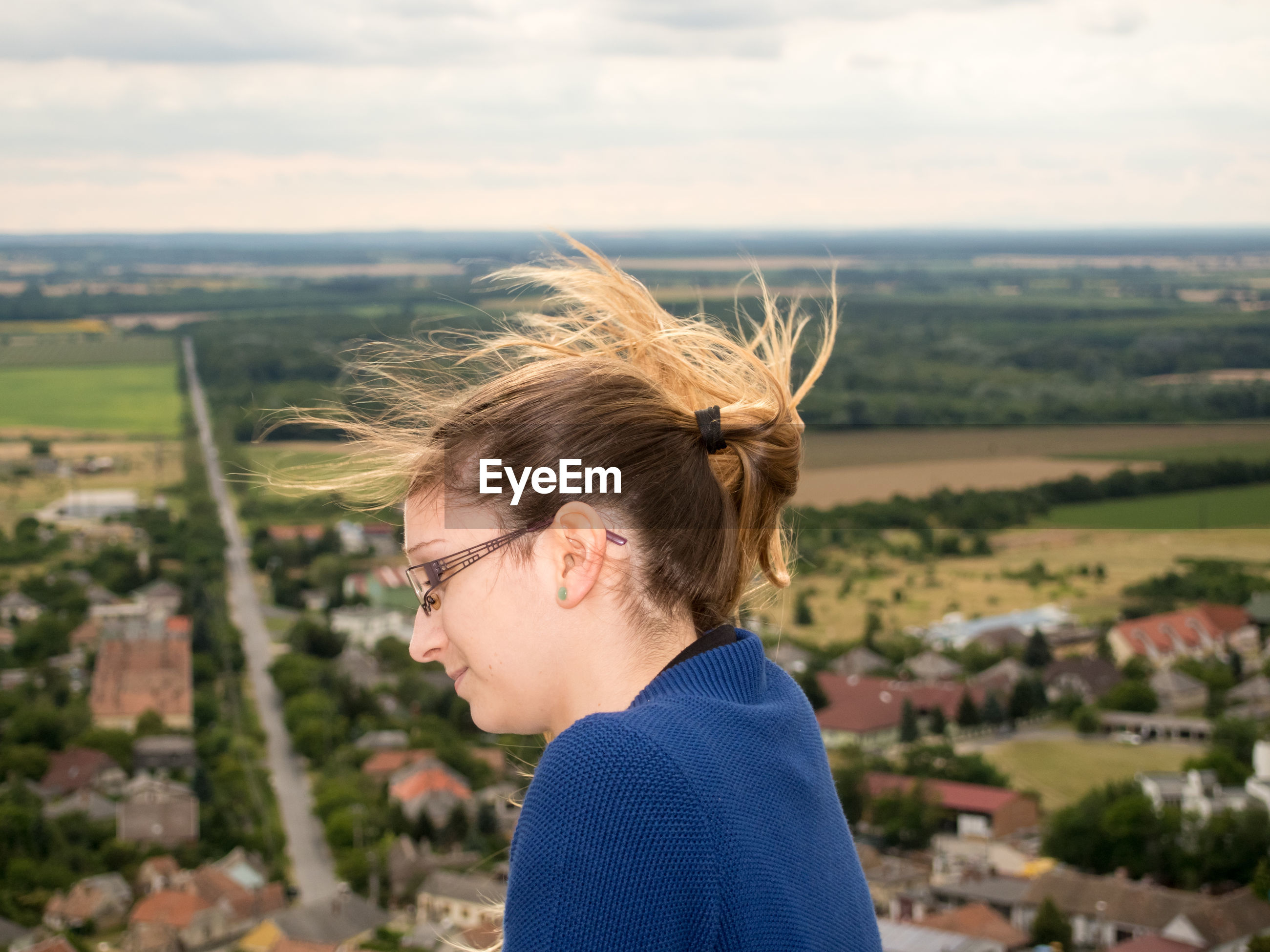 Side view of woman by landscape against sky