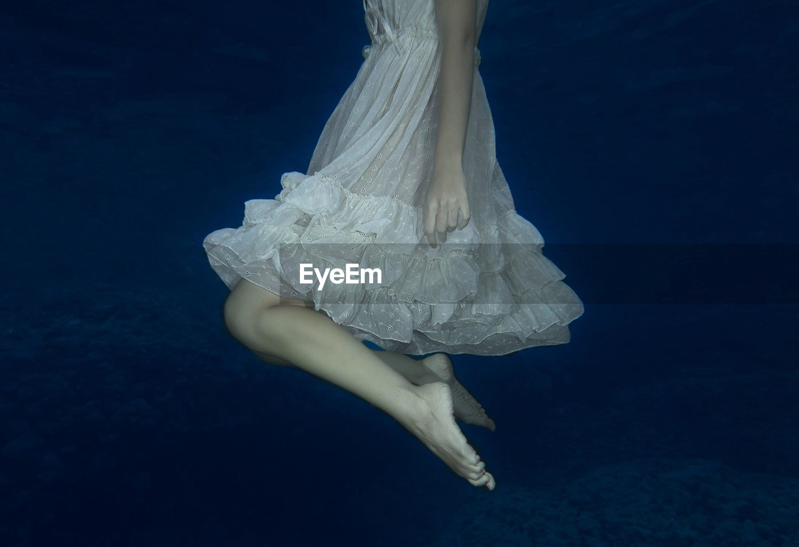 Low Section Of Woman In Dress Underwater