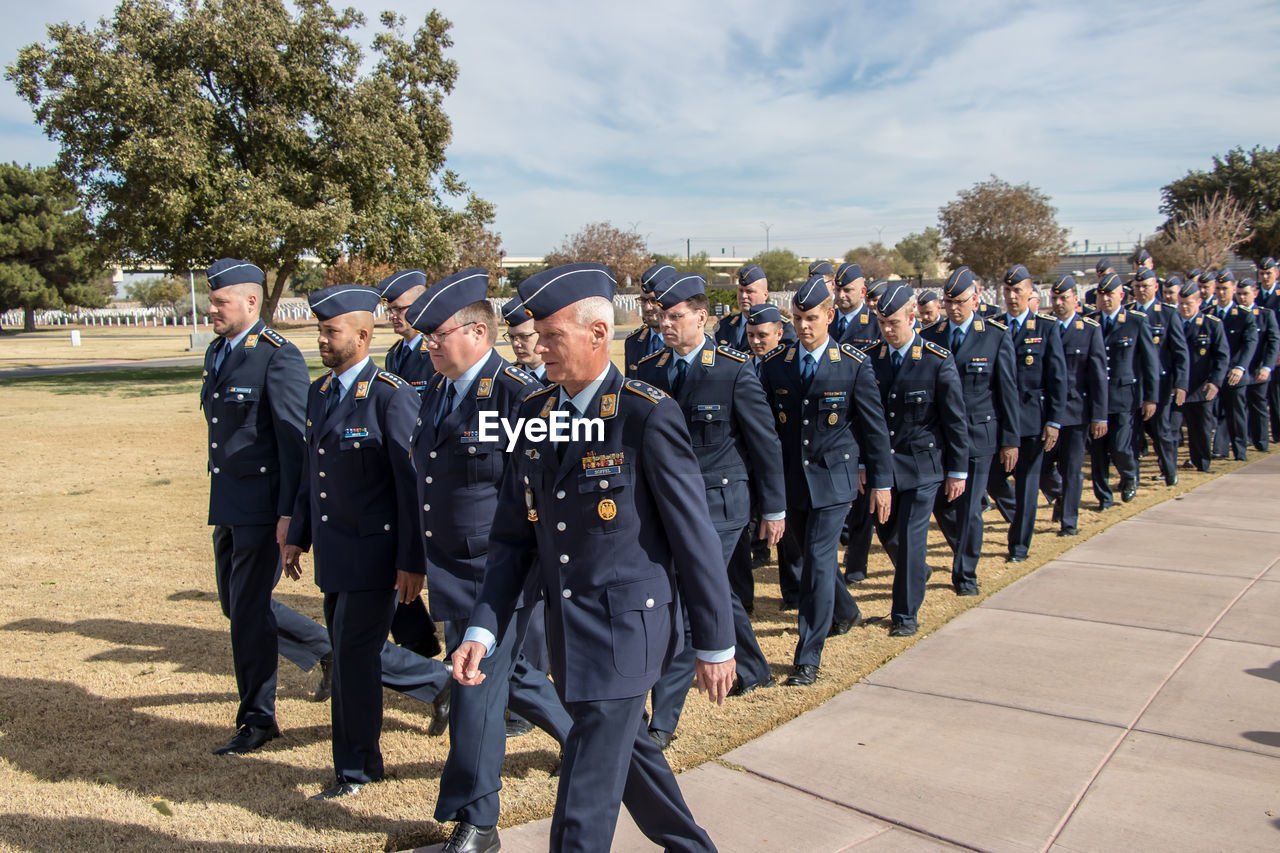 group of people, crowd, large group of people, men, real people, uniform, clothing, government, day, armed forces, event, well-dressed, military, occupation, nature, adult, outdoors, in a row, suit, responsibility, marching, respect