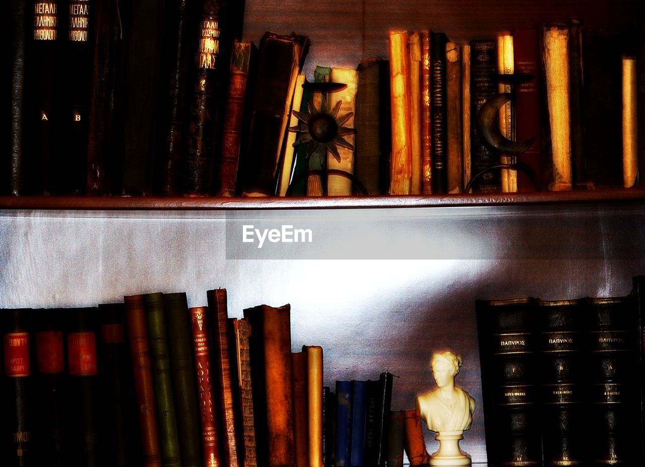 shelf, indoors, book, collection, library, textile industry, large group of objects, illuminated, standing, store, real people, bookshelf, retail, literature, men, statue, night, workshop, one person, people