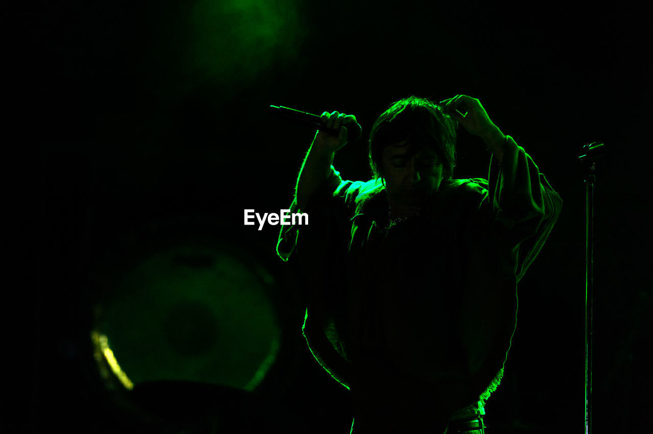 one person, green color, night, real people, arts culture and entertainment, illuminated, men, holding, performance, leisure activity, lifestyles, standing, dark, nightlife, enjoyment, black background, playing, front view, stage - performance space, stage, light, concert, music festival