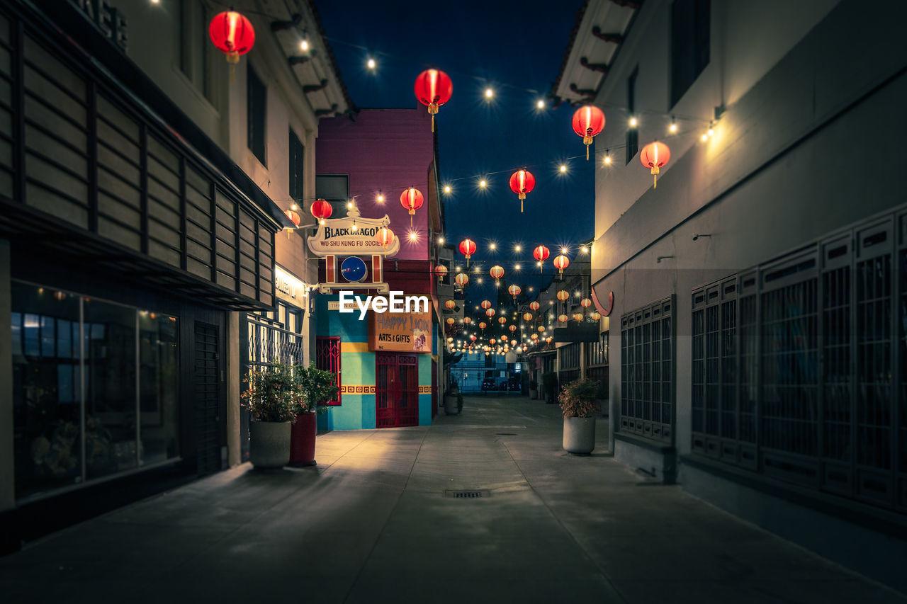 ILLUMINATED STREET LIGHT AGAINST BUILDINGS AT NIGHT