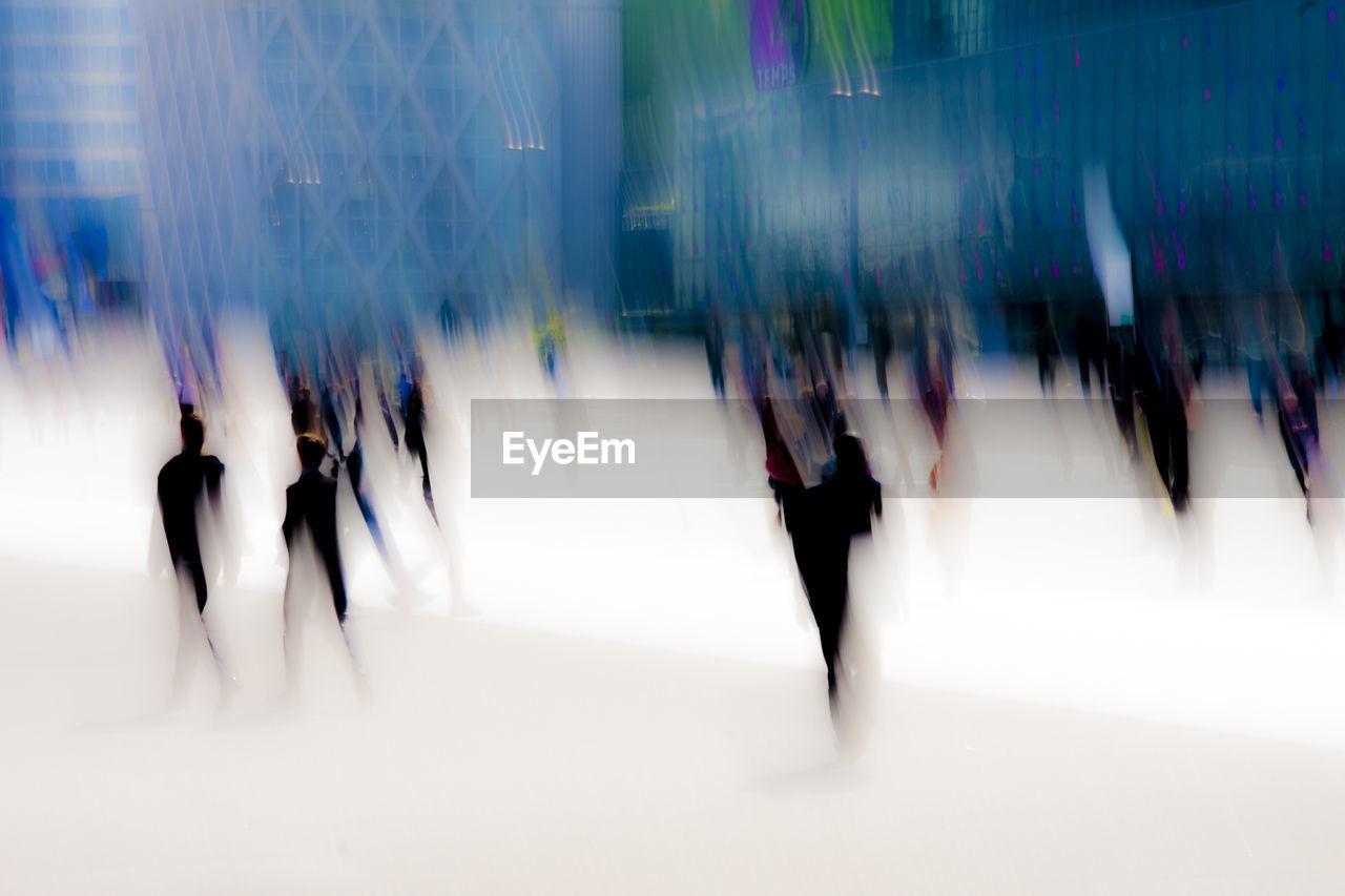 Blur Image Of People Walking Against Modern Buildings At La Defense