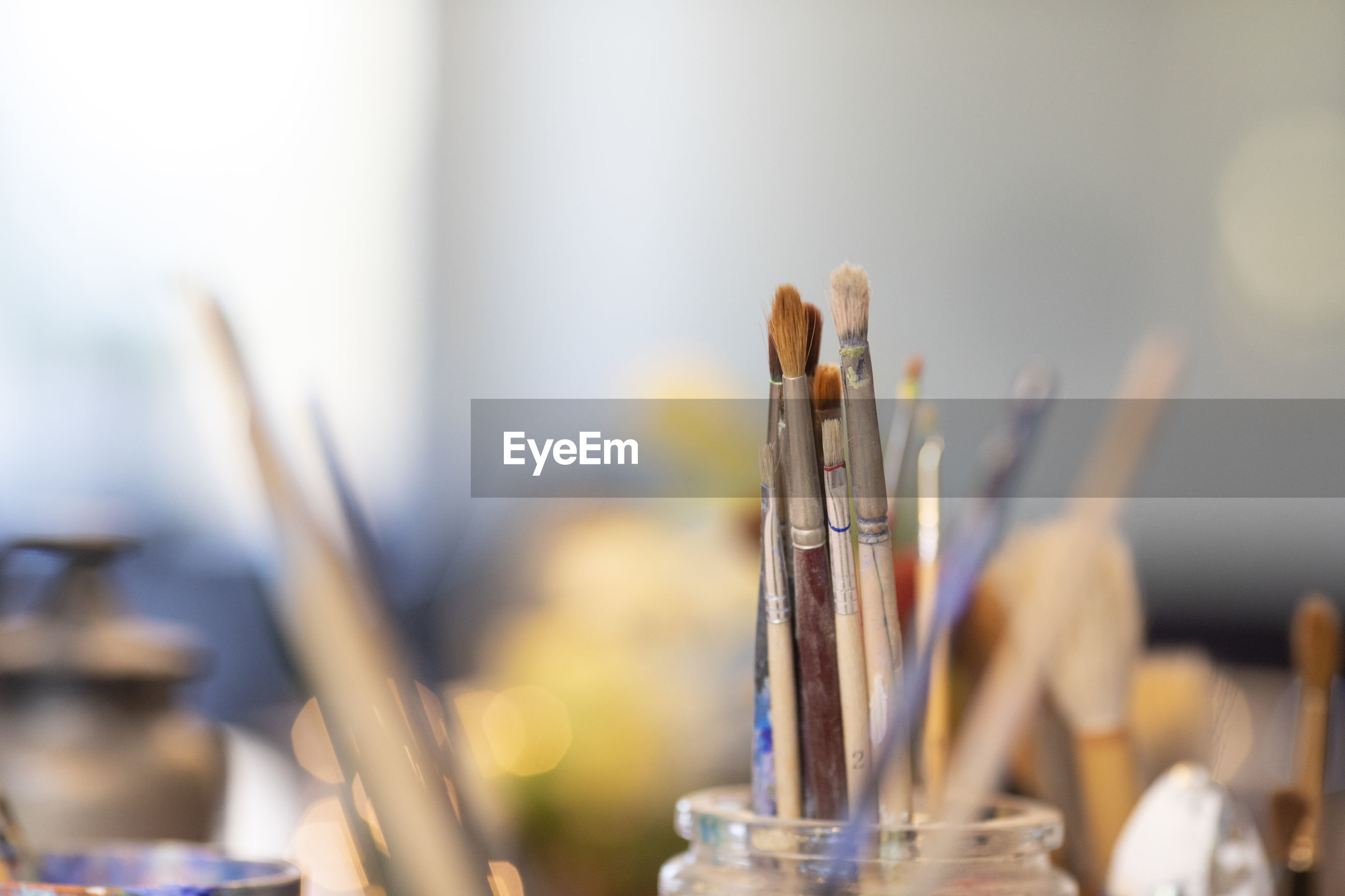 CLOSE-UP OF PAINTBRUSHES ON TABLE AGAINST BLURRED BACKGROUND
