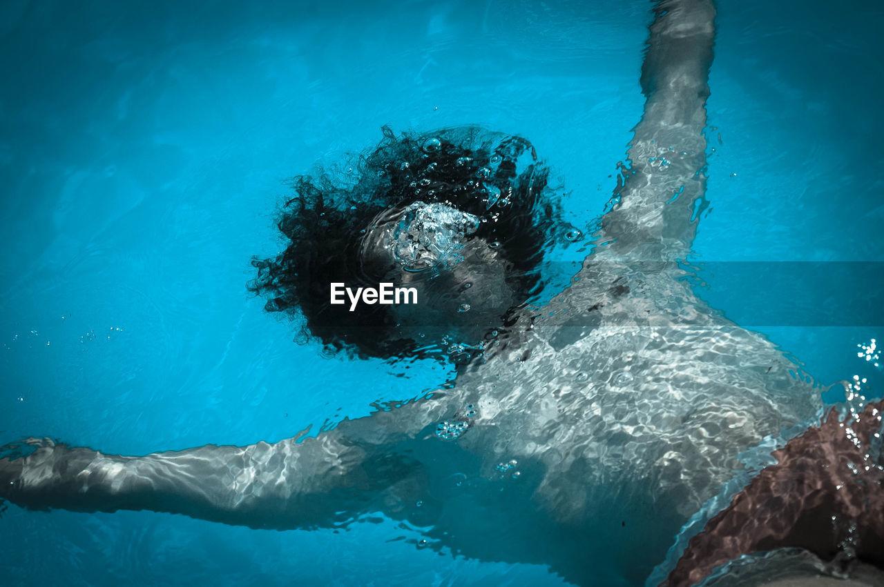 Shirtless Man Swimming In Sea