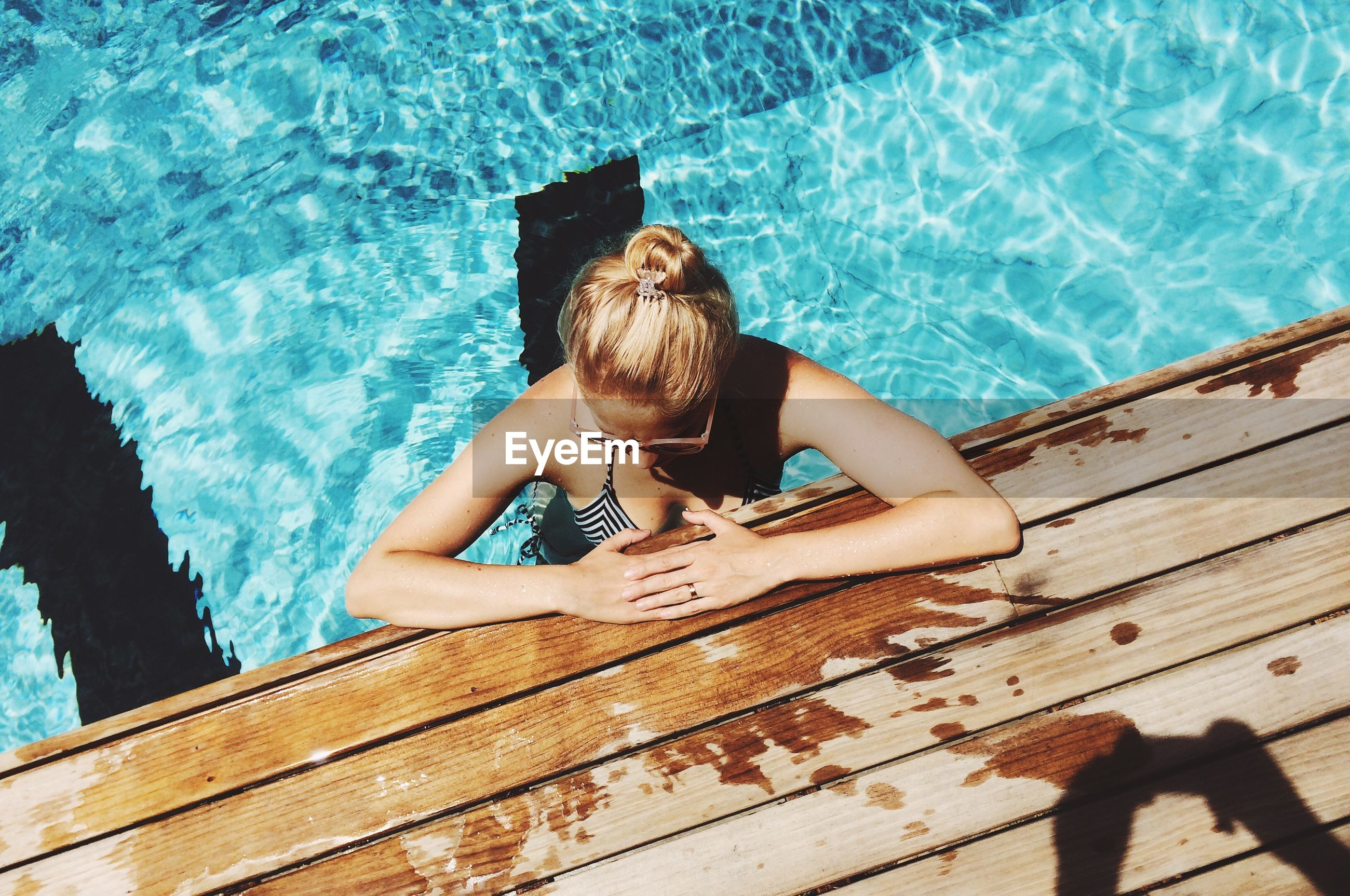 HIGH ANGLE VIEW OF YOUNG WOMAN RELAXING IN SWIMMING POOL