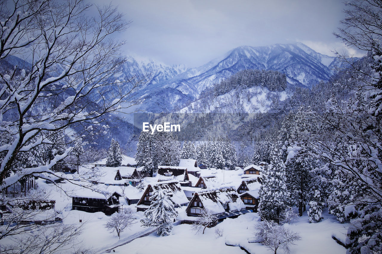 High angle view of snow covered houses and trees by mountains