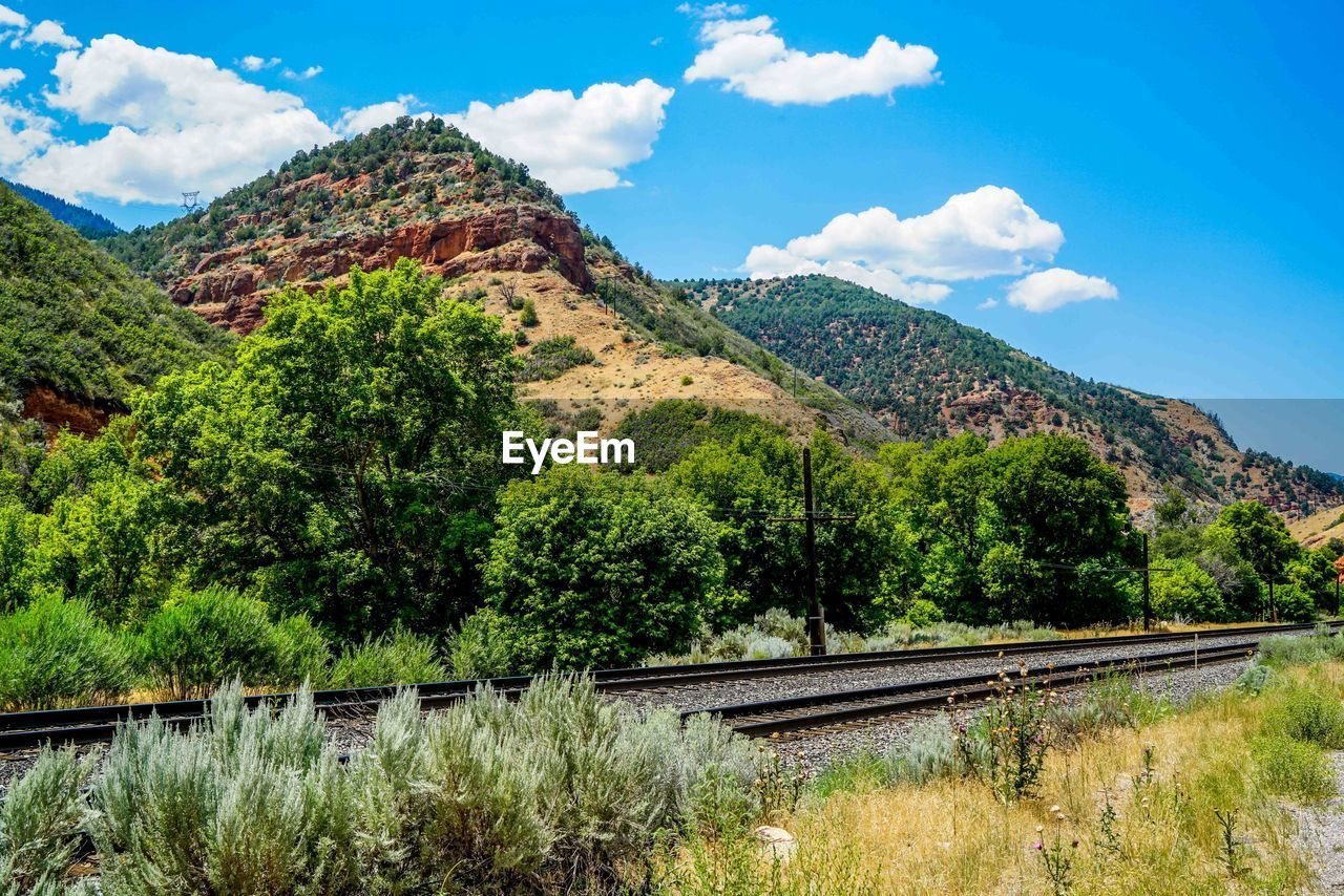 mountain, sky, tree, plant, cloud - sky, rail transportation, beauty in nature, scenics - nature, tranquil scene, nature, tranquility, day, railroad track, track, no people, transportation, landscape, environment, growth, non-urban scene, outdoors