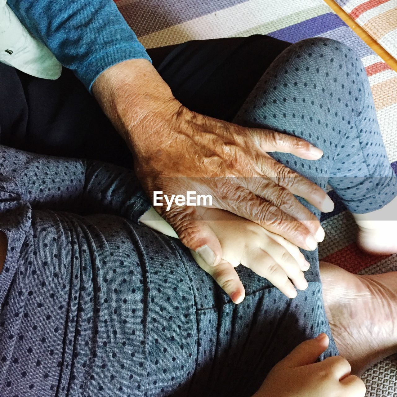 Midsection of grandmother and granddaughter at home