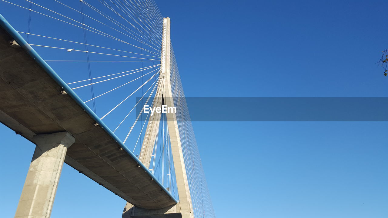 LOW ANGLE VIEW OF GOLDEN BRIDGE AGAINST CLEAR BLUE SKY
