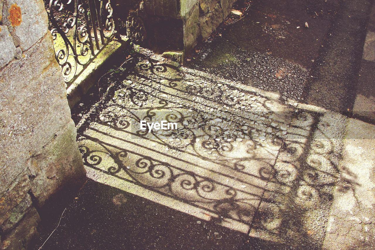Shadow of gate on sidewalk