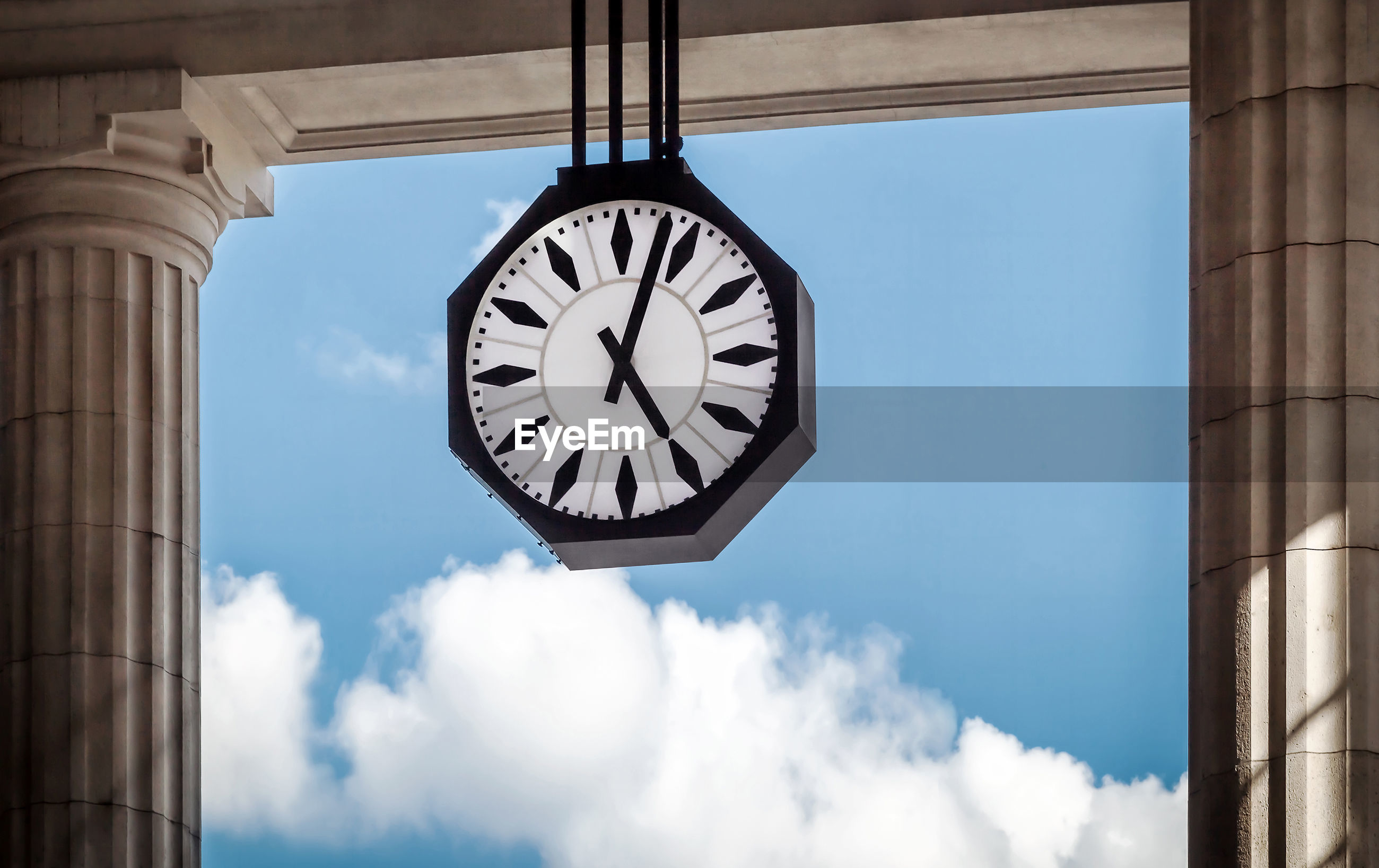 Clock hanging by columns against sky