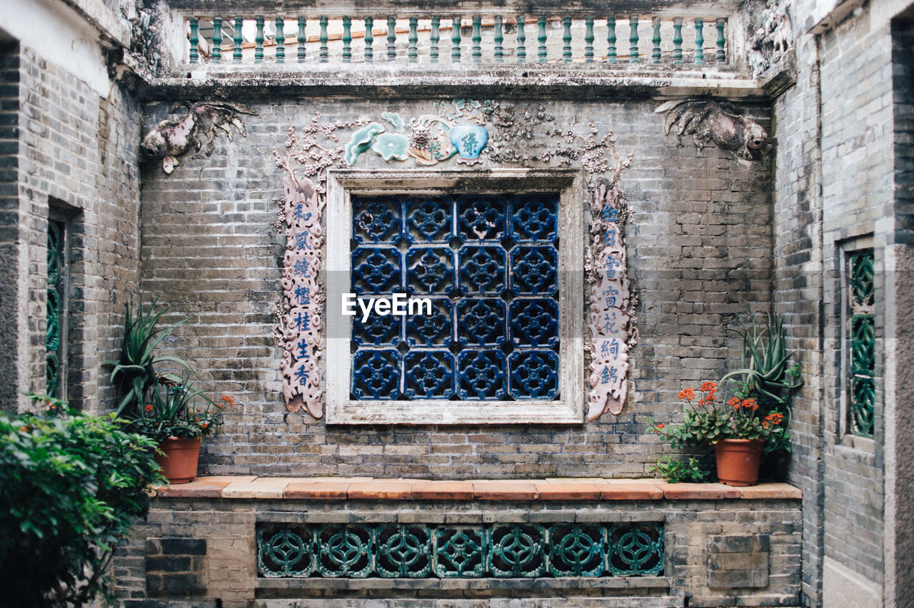 built structure, building exterior, architecture, window, day, building, no people, wall, wall - building feature, low angle view, potted plant, plant, door, entrance, outdoors, pattern, house, brick, the past, history, ornate, stone wall