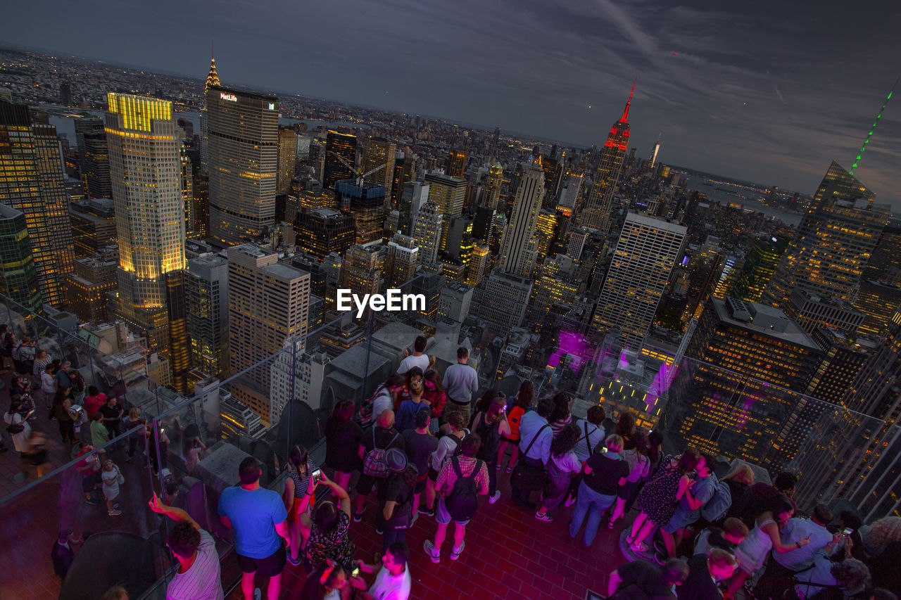 HIGH ANGLE VIEW OF CROWD AT ILLUMINATED CITY BUILDINGS