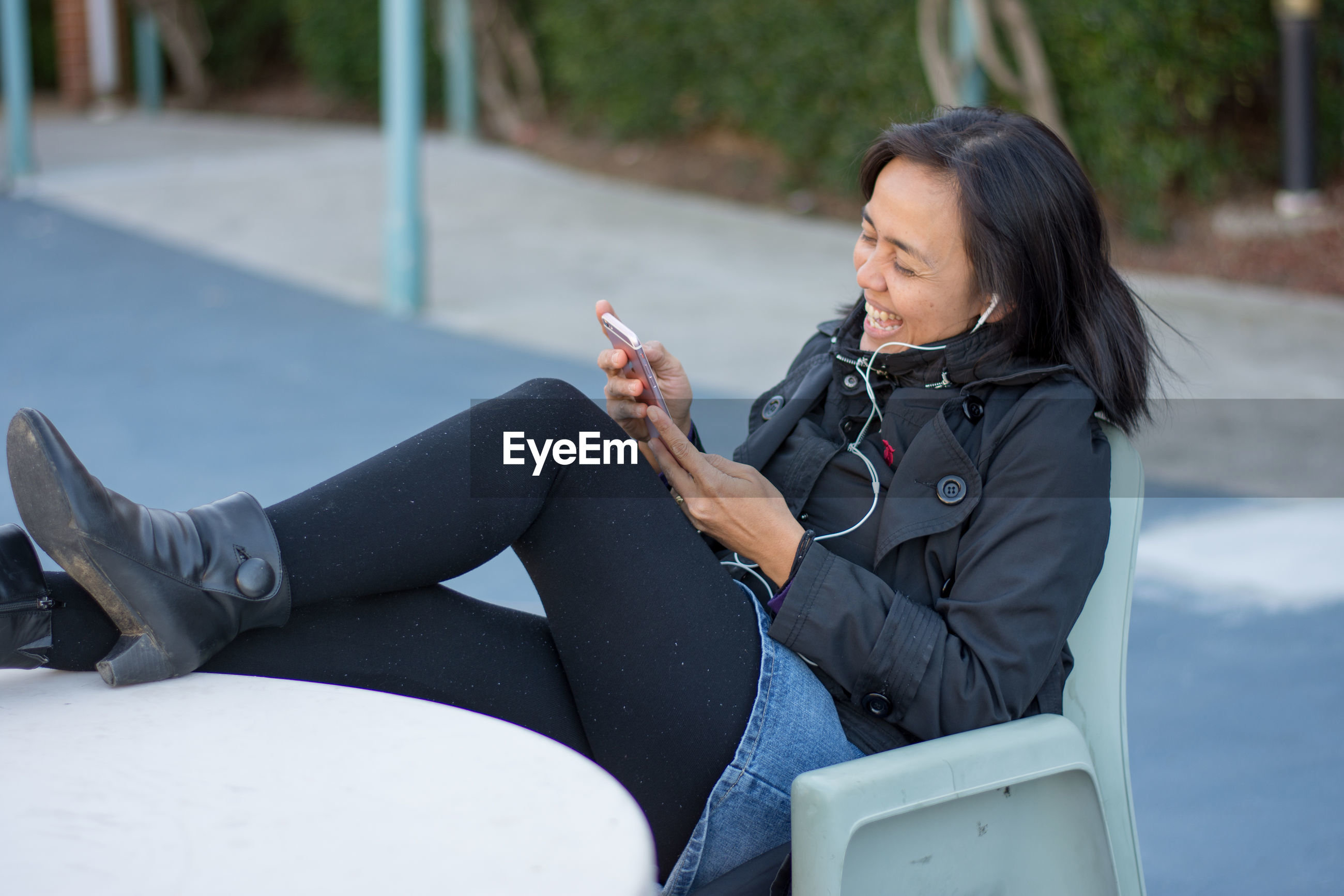 Mid adult woman using mobile phone while sitting on chair