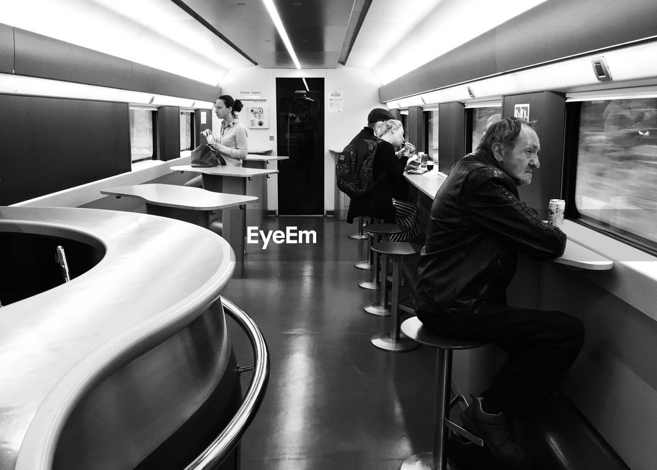 public transportation, real people, rail transportation, train, transportation, train - vehicle, mode of transportation, group of people, lifestyles, seat, men, indoors, illuminated, vehicle interior, travel, people, women, adult, journey, subway train