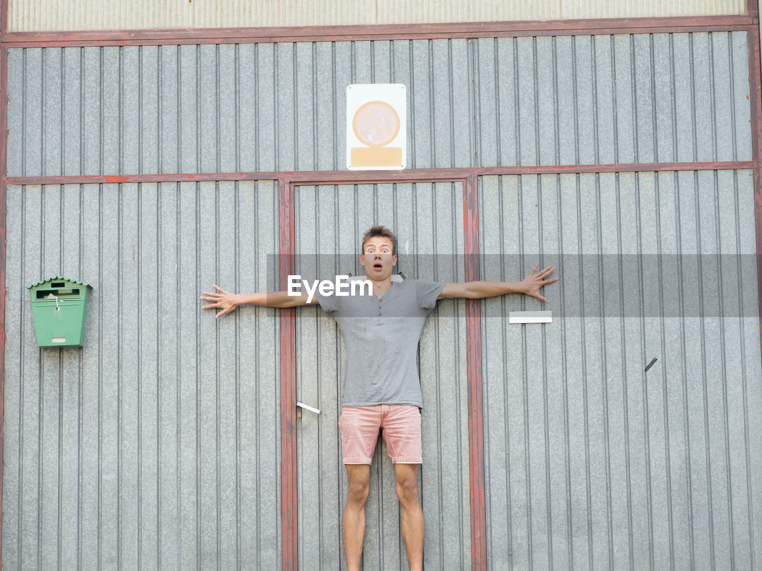 Portrait of shocked young man with arms outstretched against metallic door