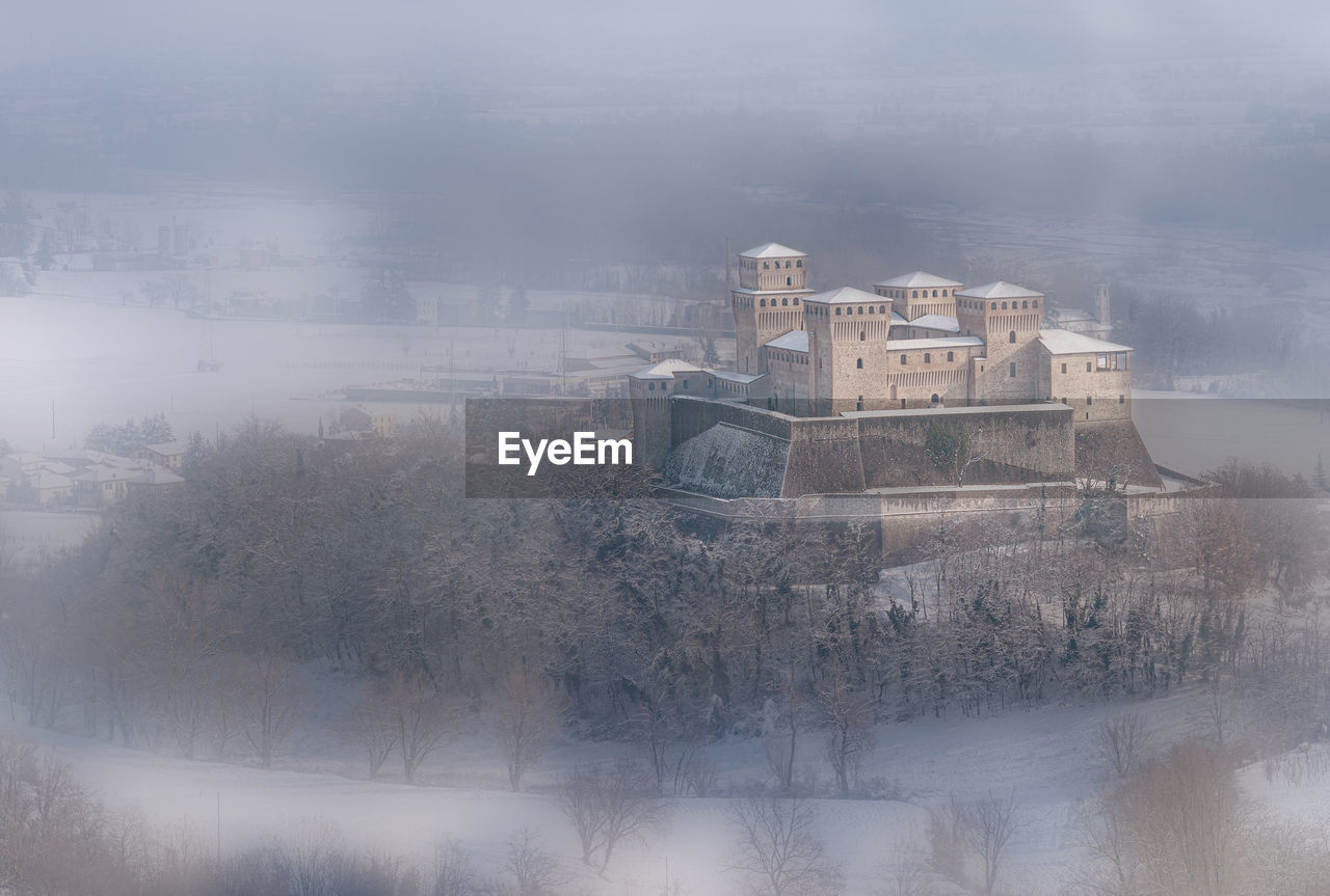 fog, architecture, building exterior, built structure, tree, nature, building, plant, no people, sky, day, outdoors, travel destinations, history, the past, cold temperature, old, high angle view, winter, digital composite