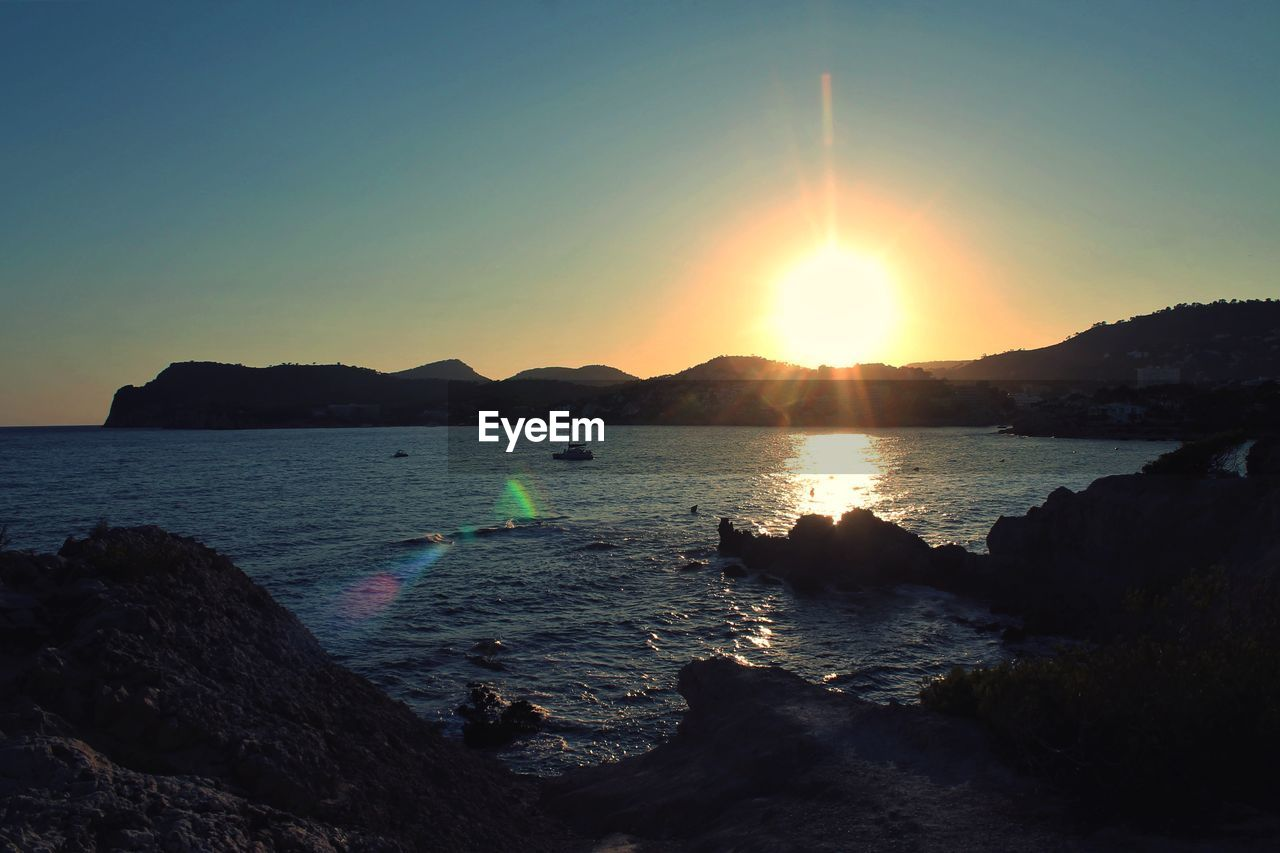 water, sky, scenics - nature, beauty in nature, sea, sunset, sunlight, sun, tranquility, nature, tranquil scene, mountain, land, non-urban scene, clear sky, idyllic, sunbeam, beach, lens flare, outdoors, no people, bright