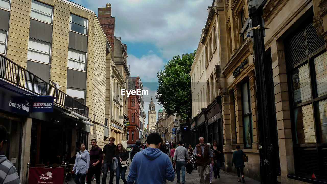architecture, building exterior, built structure, sky, walking, city, large group of people, real people, men, day, women, outdoors, people