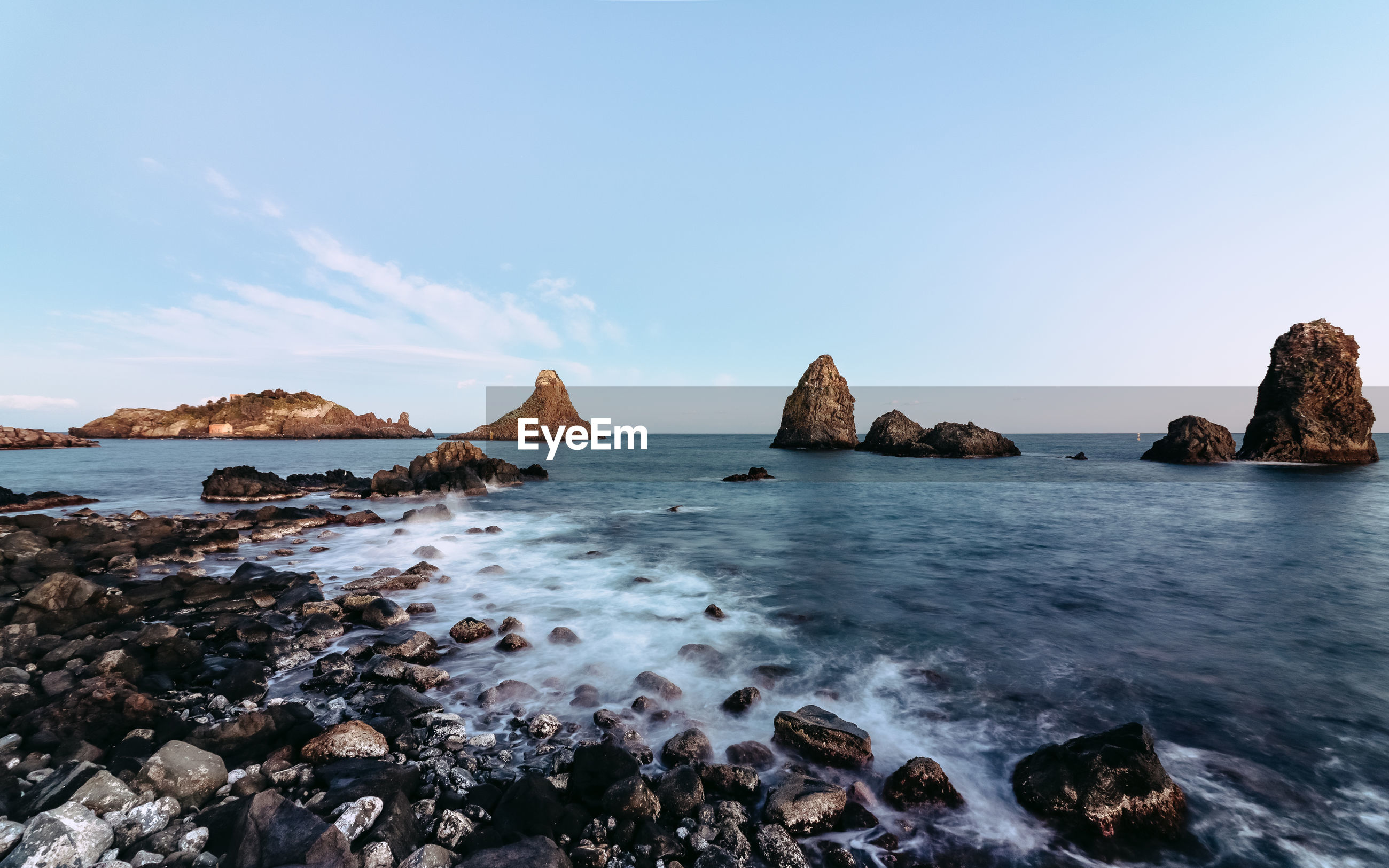 Scenic view of sea and rocks against clear sky