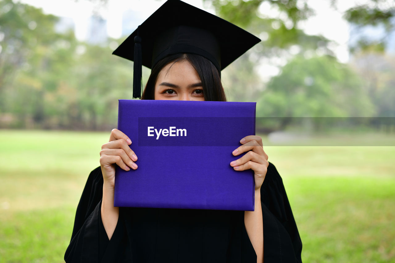 education, graduation, graduation gown, student, university, university student, learning, achievement, mortarboard, holding, front view, school, real people, focus on foreground, book, one person, success, publication, portrait, outdoors, obscured face