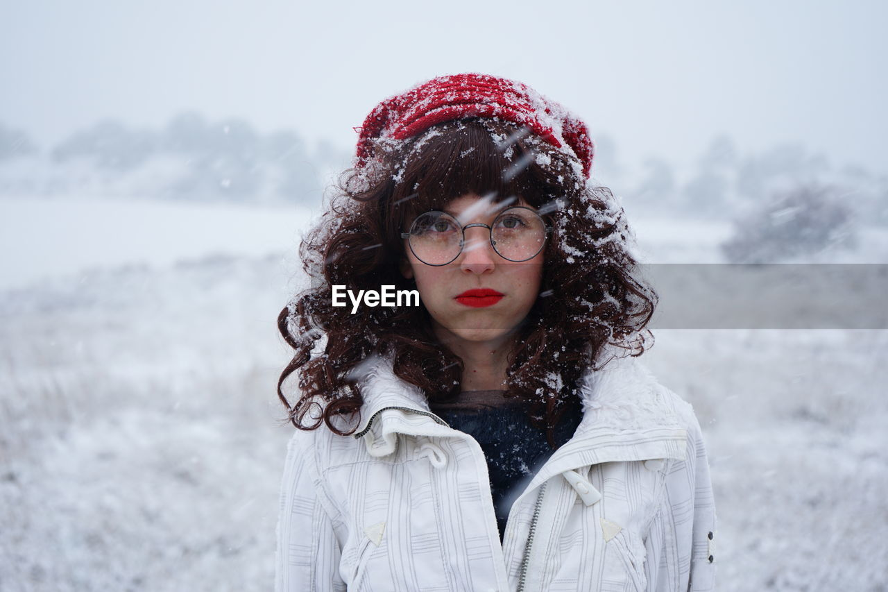 Portrait Of Young Woman Standing On Field During Snowfall