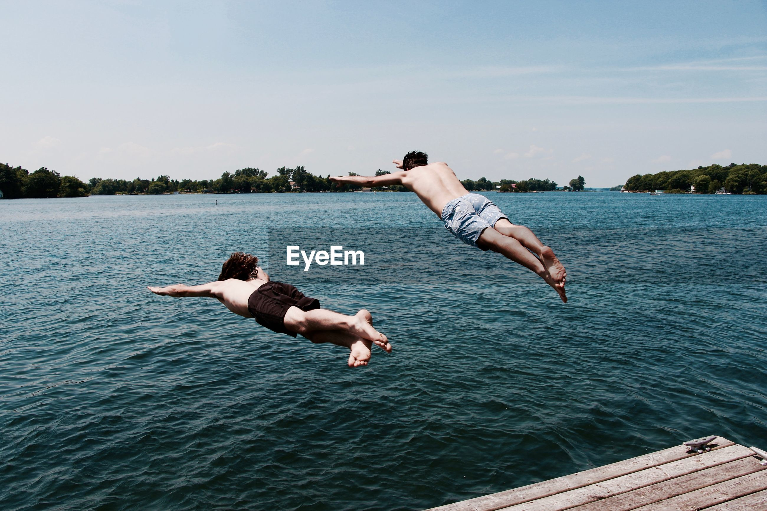 Shirtless friends jumping into river against sky
