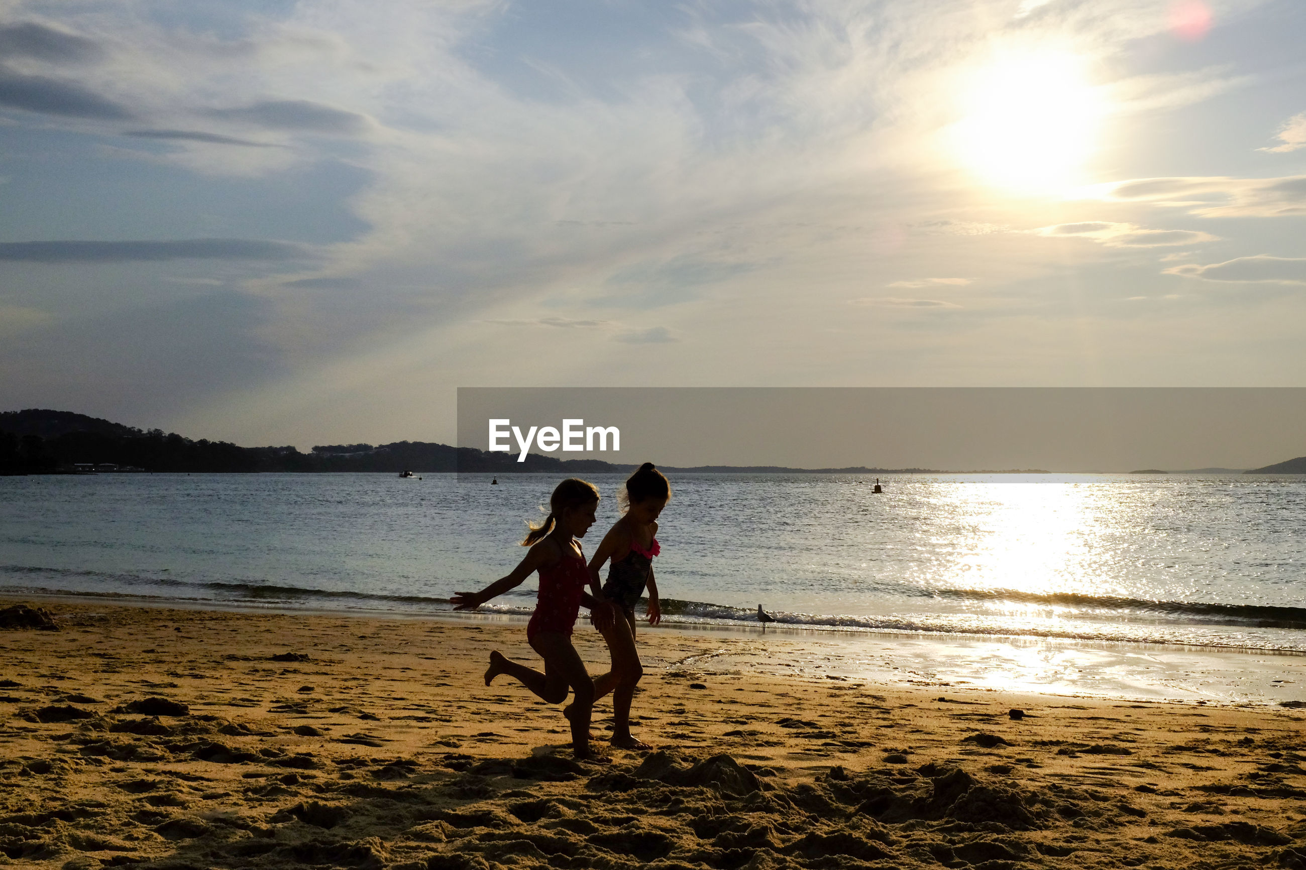 COUPLE ON BEACH AGAINST SKY DURING SUNSET