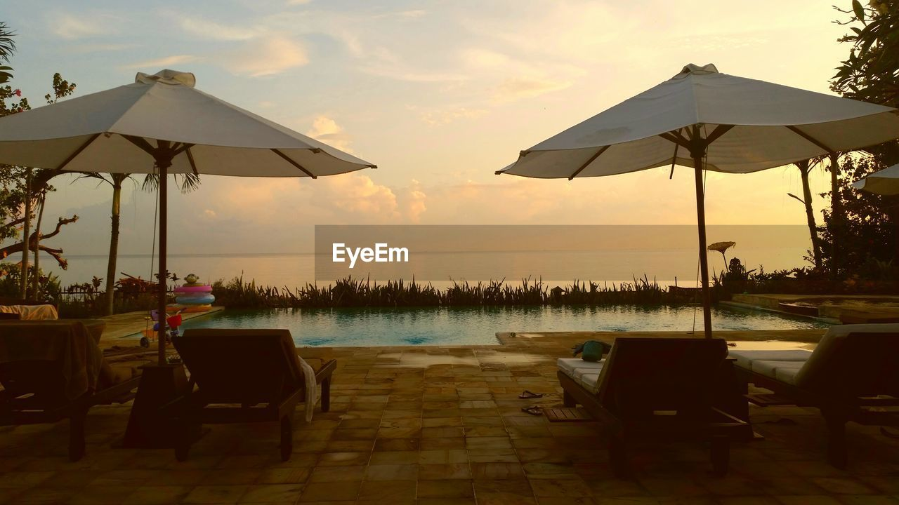 Umbrellas And Lounge Chairs By Swimming Pool Against Sky During Sunset
