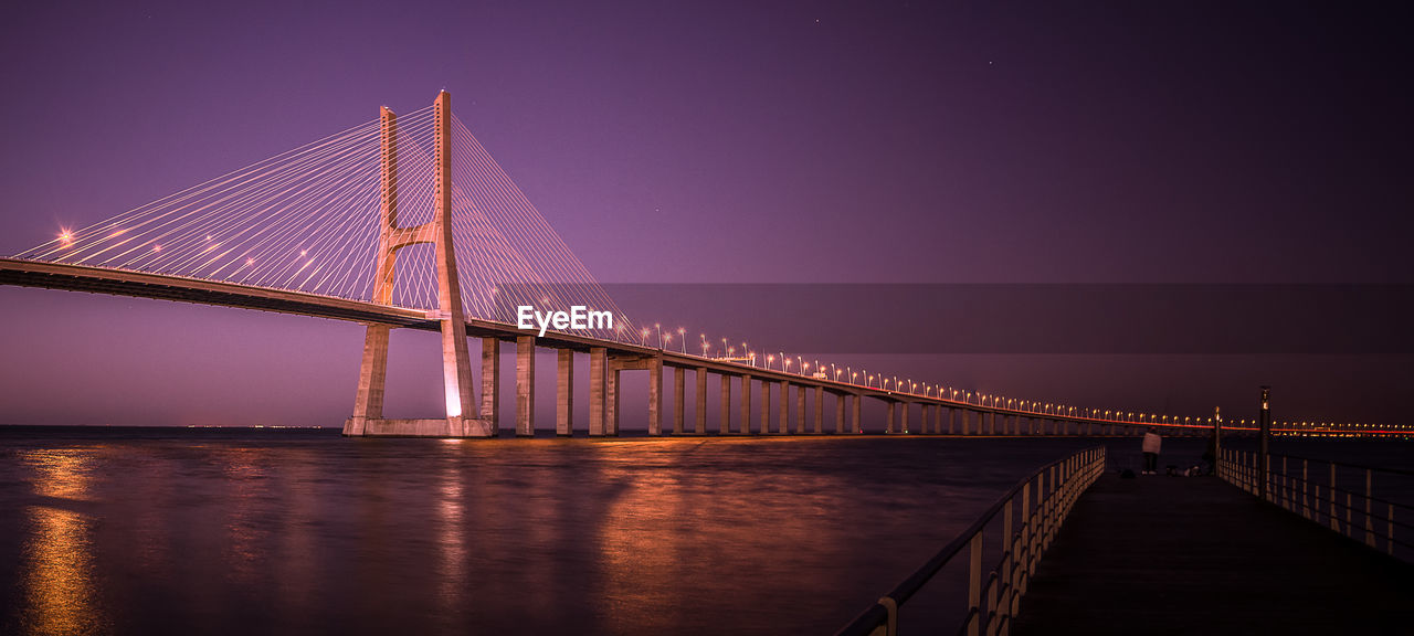 Low Angle View Of Vasco Da Gama Bridge Over River Against Clear Sky At Dusk