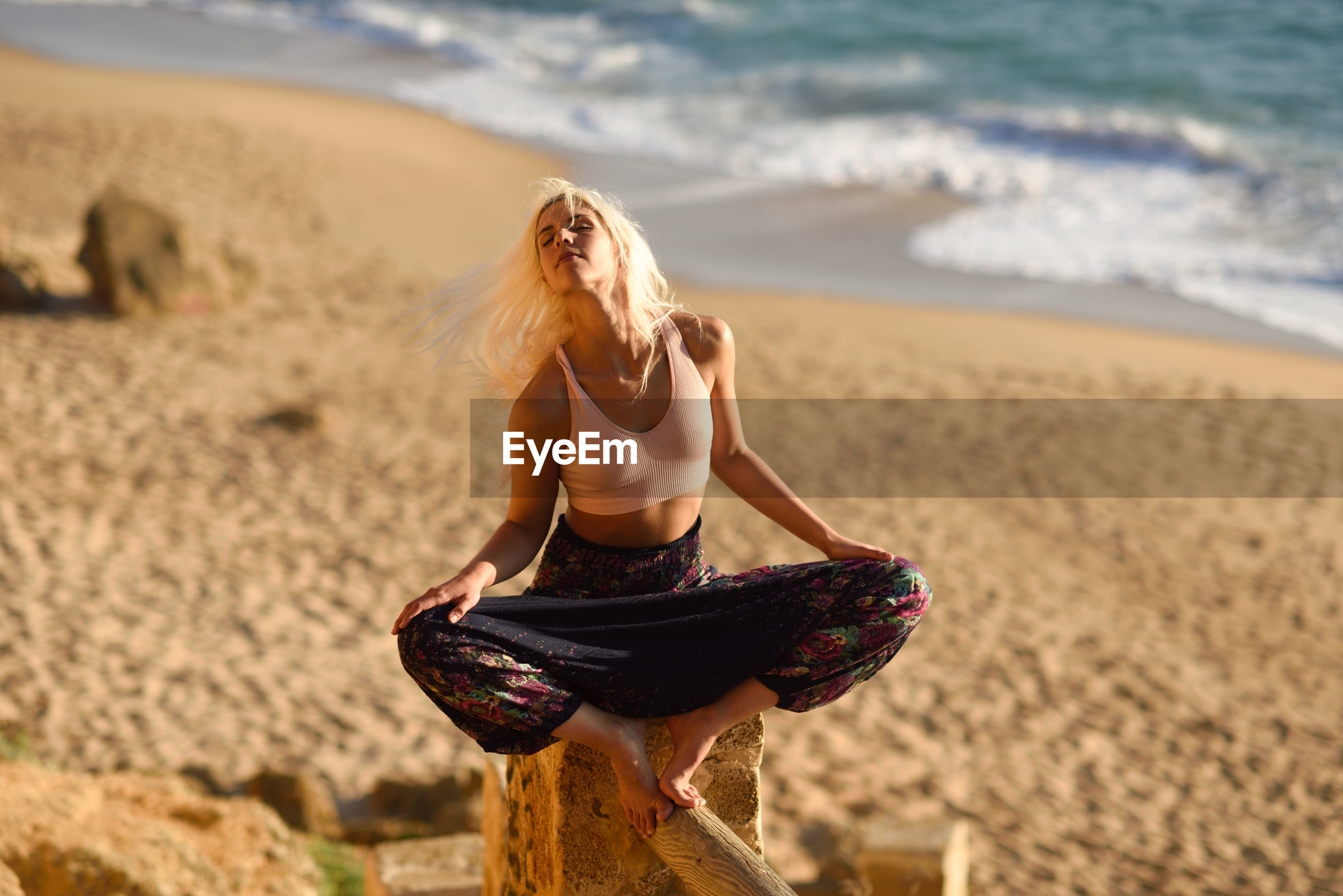 Young woman meditating while sitting on rock at beach against sky