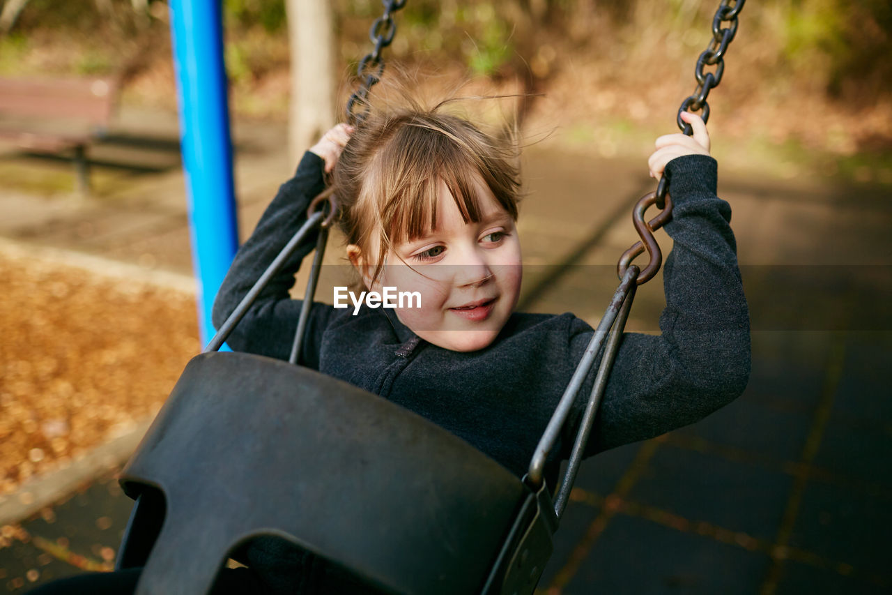 childhood, child, playground, swing, portrait, happiness, one person, girls, looking at camera, day, leisure activity, sitting, smiling, enjoyment, front view, innocence, outdoor play equipment, females, outdoors