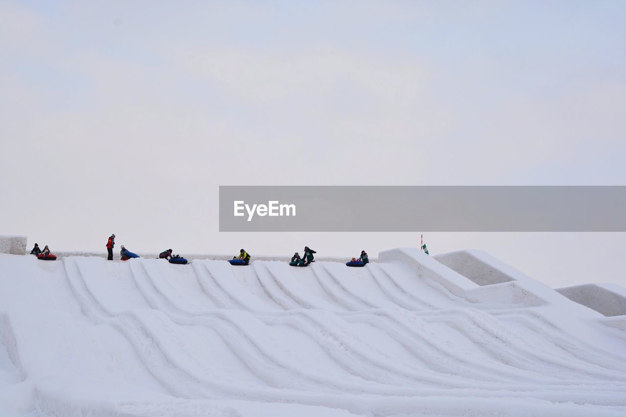 People on tobogganing on snow covered land against sky