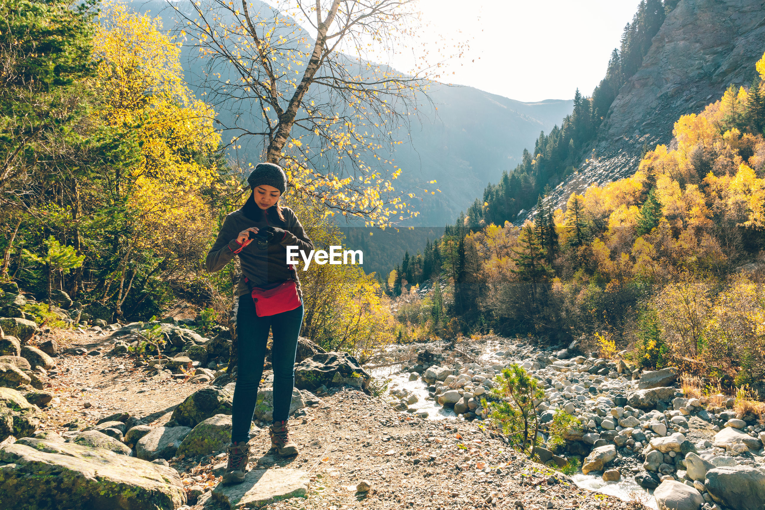 Full length of woman standing by stream against trees and mountains