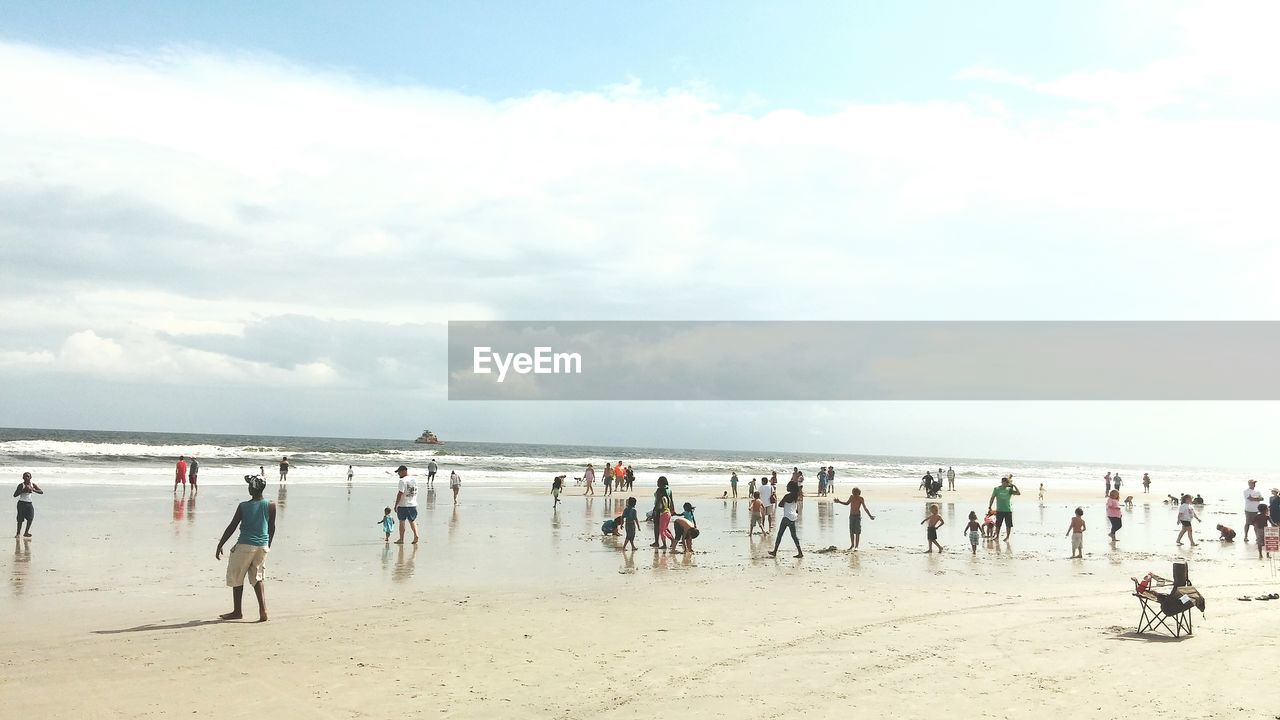 beach, large group of people, sky, sea, sand, nature, water, real people, cloud - sky, day, outdoors, horizon over water, lifestyles, beauty in nature, men, beach volleyball, people, adult
