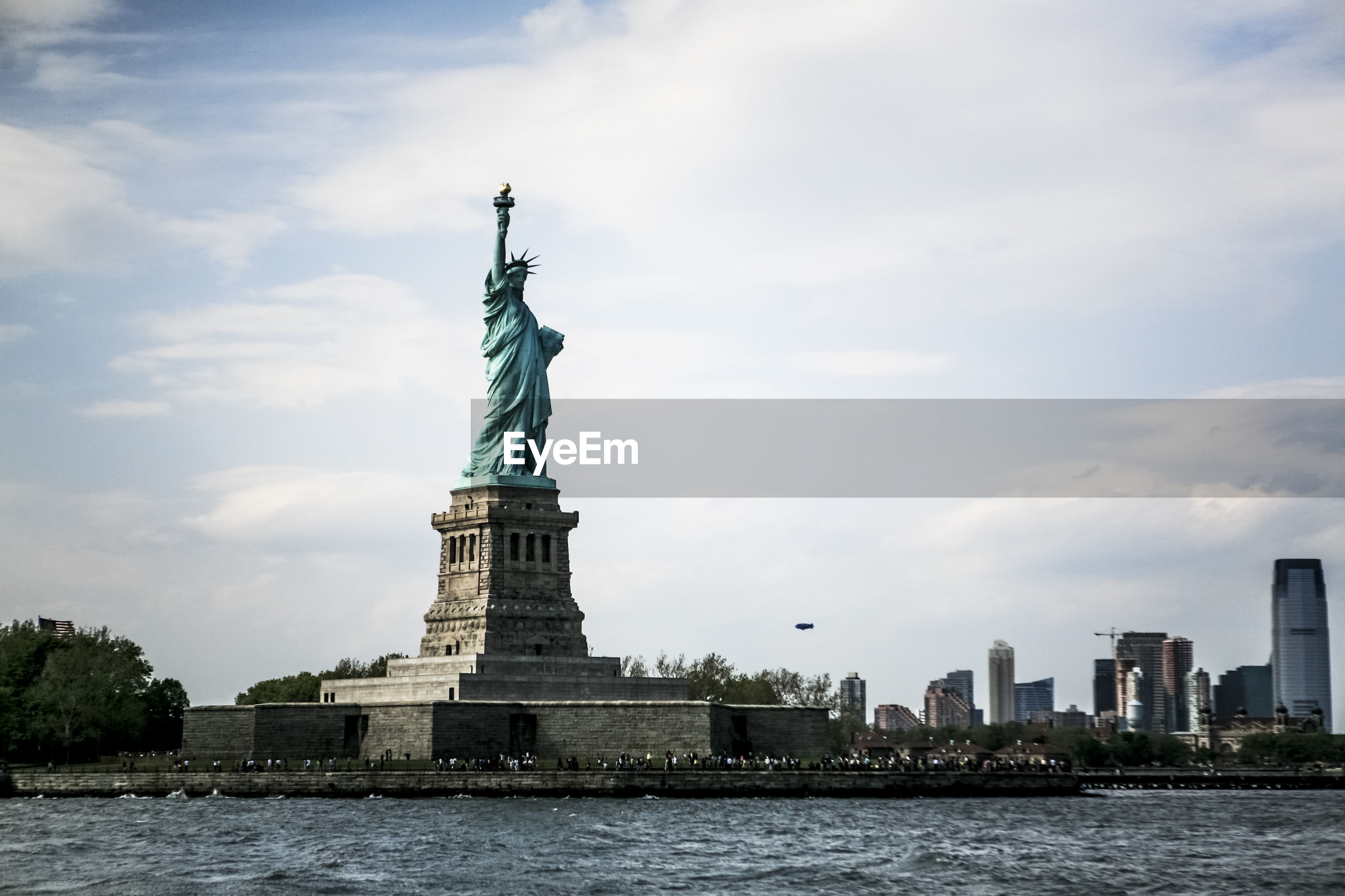 Low angle view of statue of liberty in city against cloudy sky