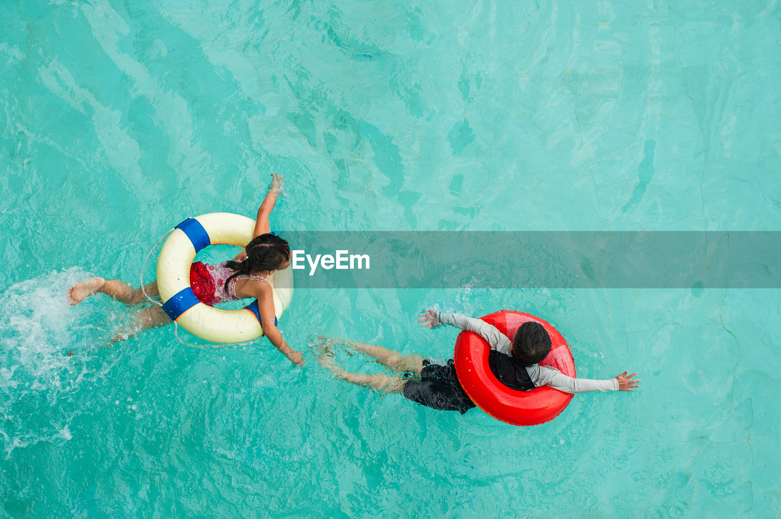 HIGH ANGLE VIEW OF COUPLE SWIMMING IN POOL