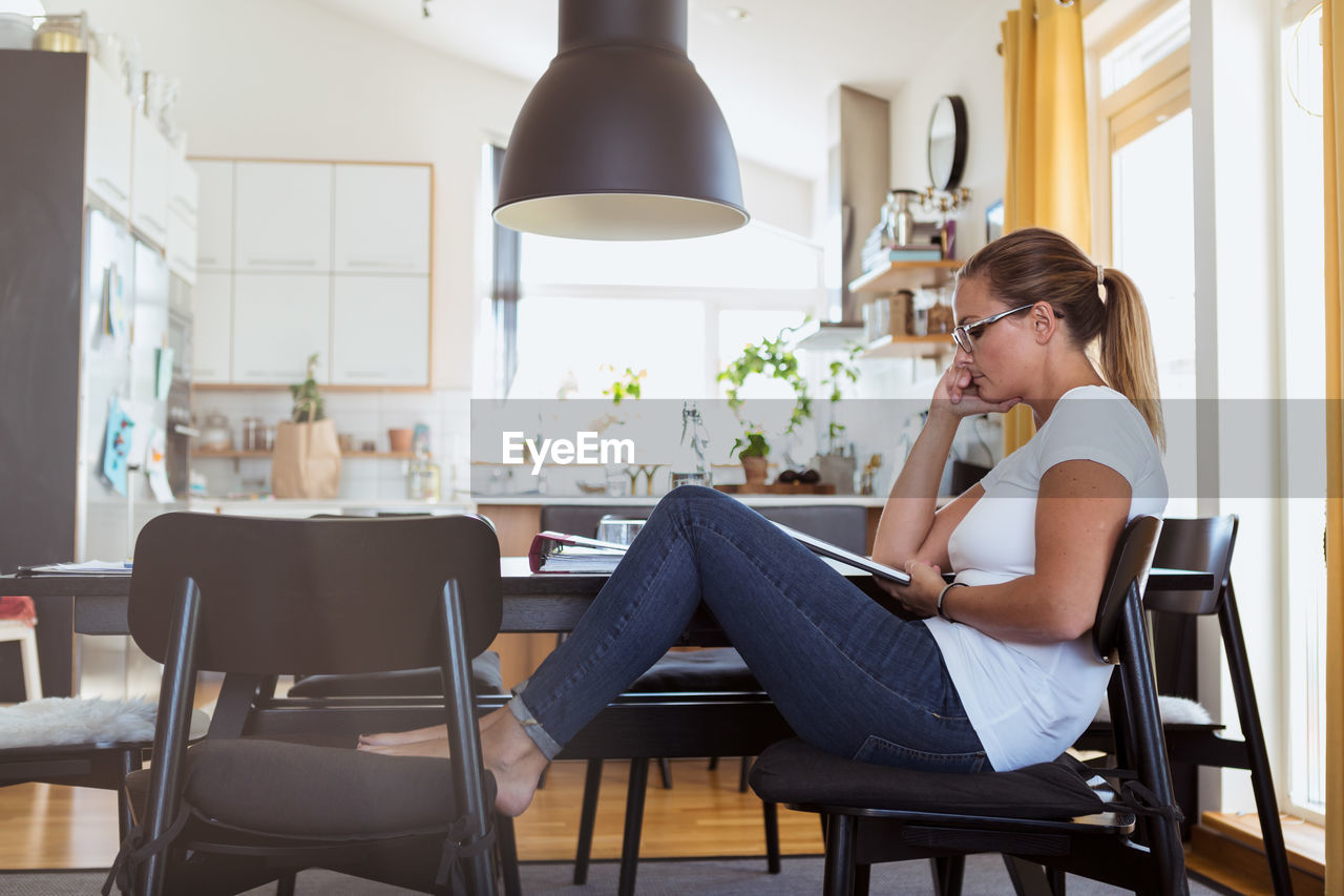 SIDE VIEW OF WOMAN SITTING ON CHAIR IN TABLE