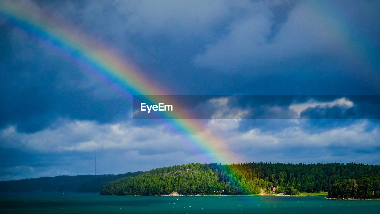 beauty in nature, rainbow, scenics - nature, cloud - sky, water, tranquility, sky, tree, tranquil scene, idyllic, nature, multi colored, lake, day, no people, double rainbow, plant, non-urban scene, outdoors